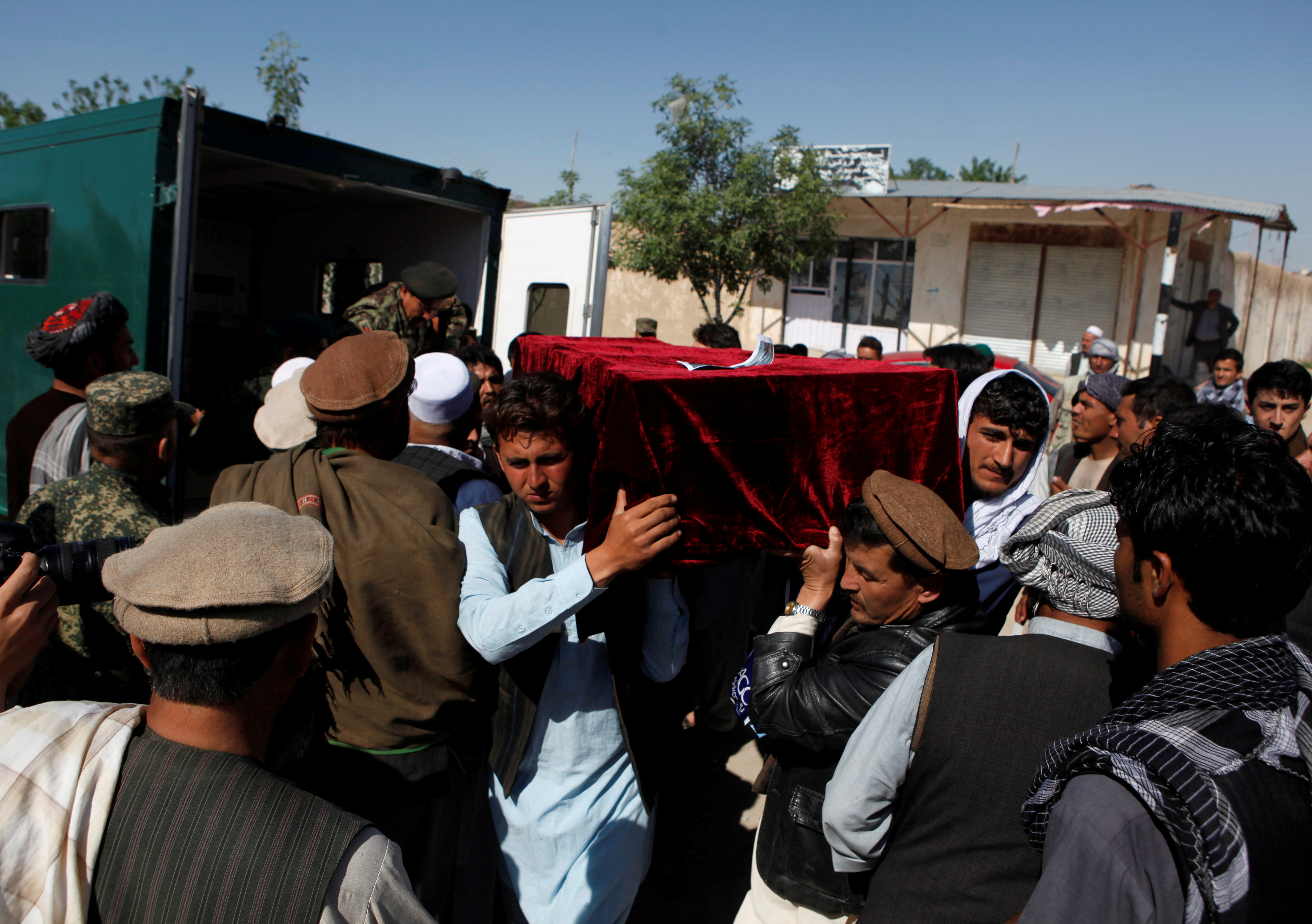 FILE - Relatives carry the coffin of one of the victims a day after an attack on an army headquarters in Mazar-i-Sharif, northern Afghanistan, April 22, 2017.
