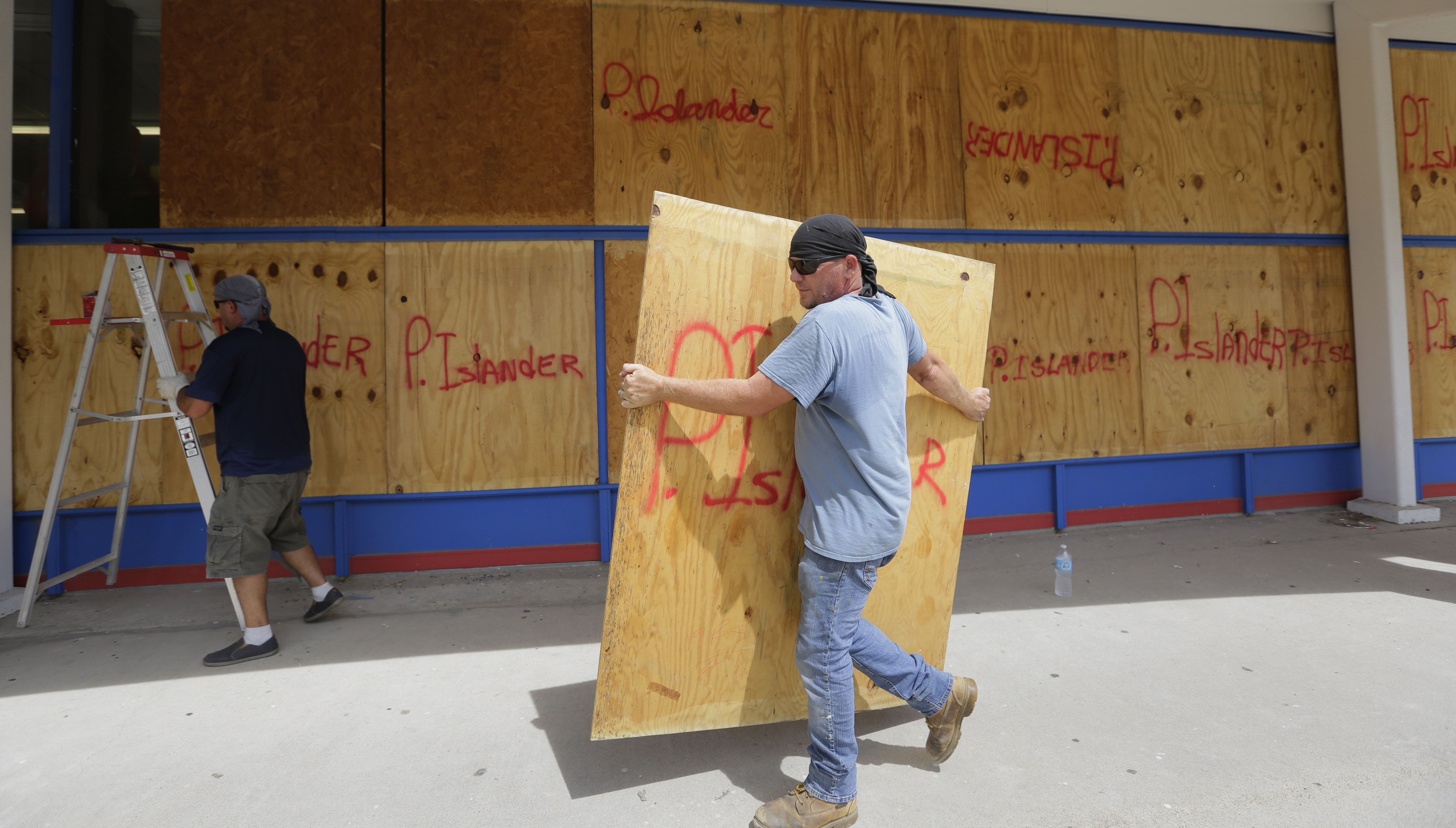 James Redford carries a sheet of plywood as he helps board up windows in preparation for Hurricane Harvey in Corpus Christi, Texas, Aug. 24, 2017.