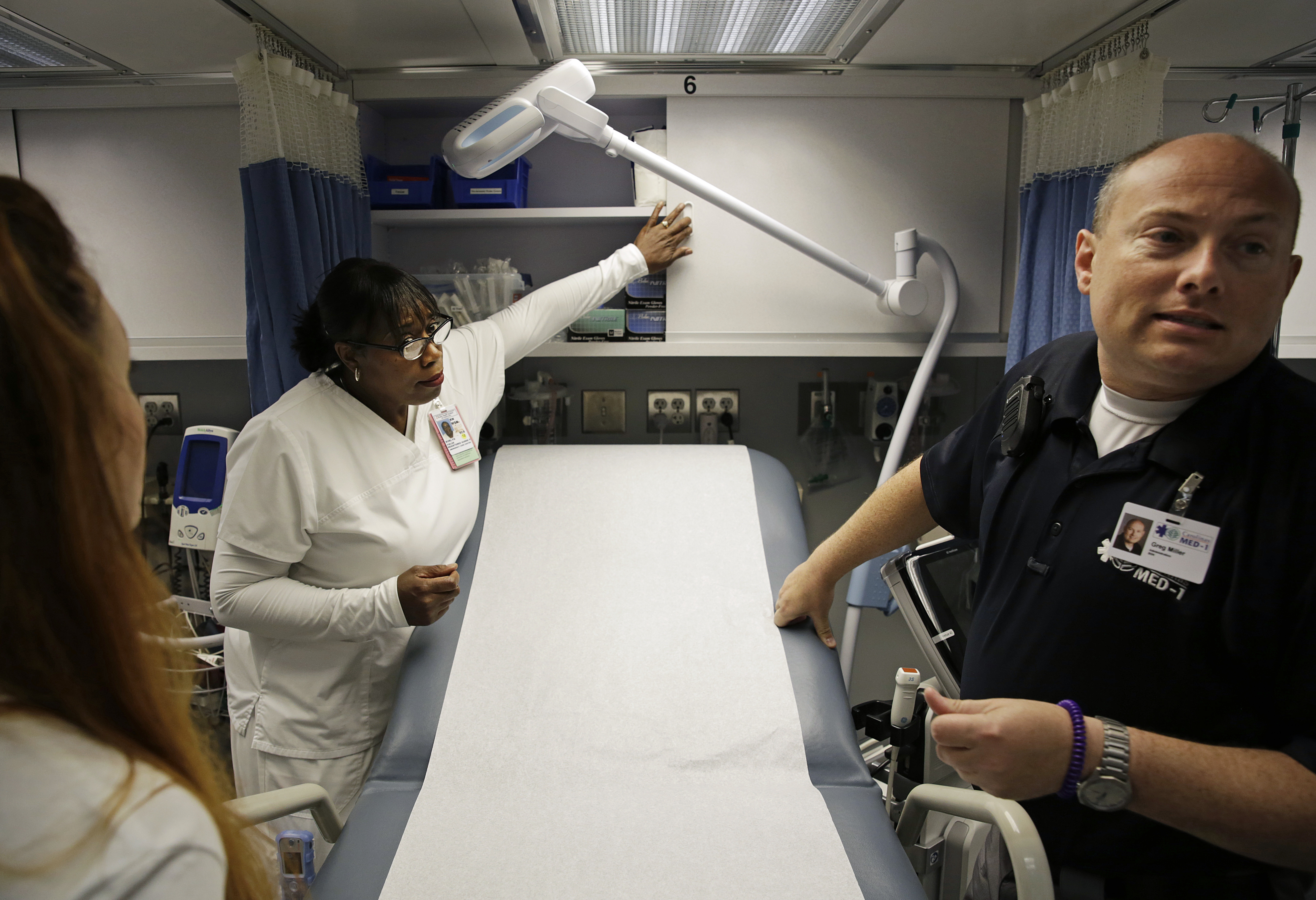 Nurses Tessa Sheffield, from left, Evelyn Fields and Greg Miller look over a mobile emergency room set up outside Grady Memorial Hospital to help handle the ever-growing number of flu cases in Atlanta, Jan. 29, 2018.