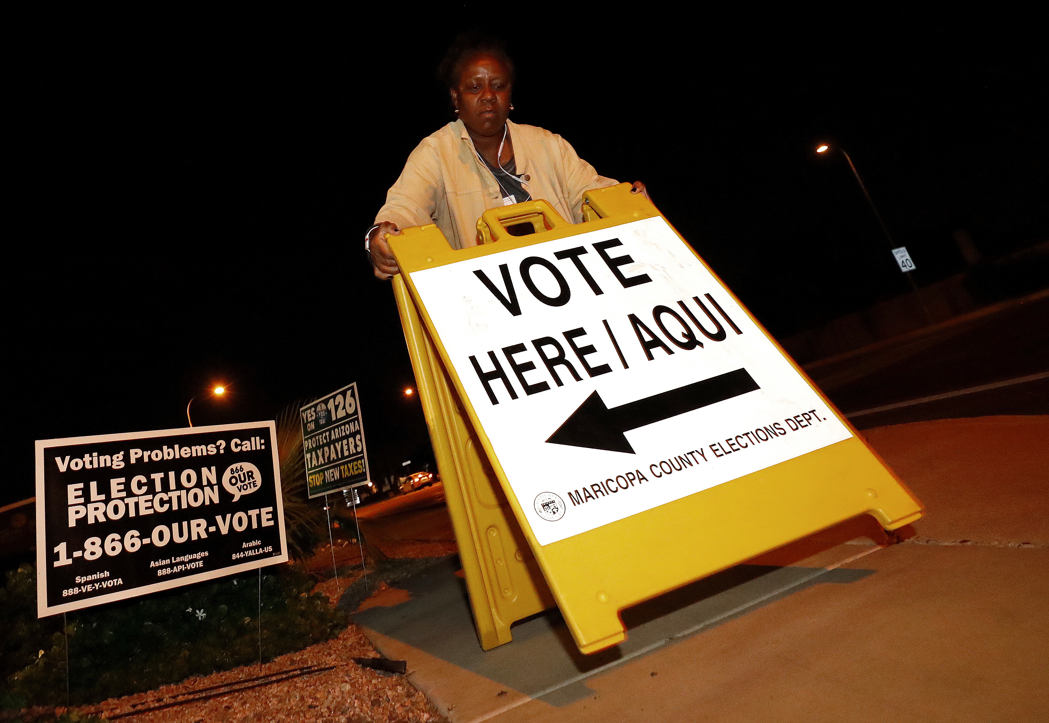 """Maricopa County elections official Deborah Atkins places a """"vote"""" sign outside a polling station prior to its opening, Nov. 6, 2018, in Phoenix."""