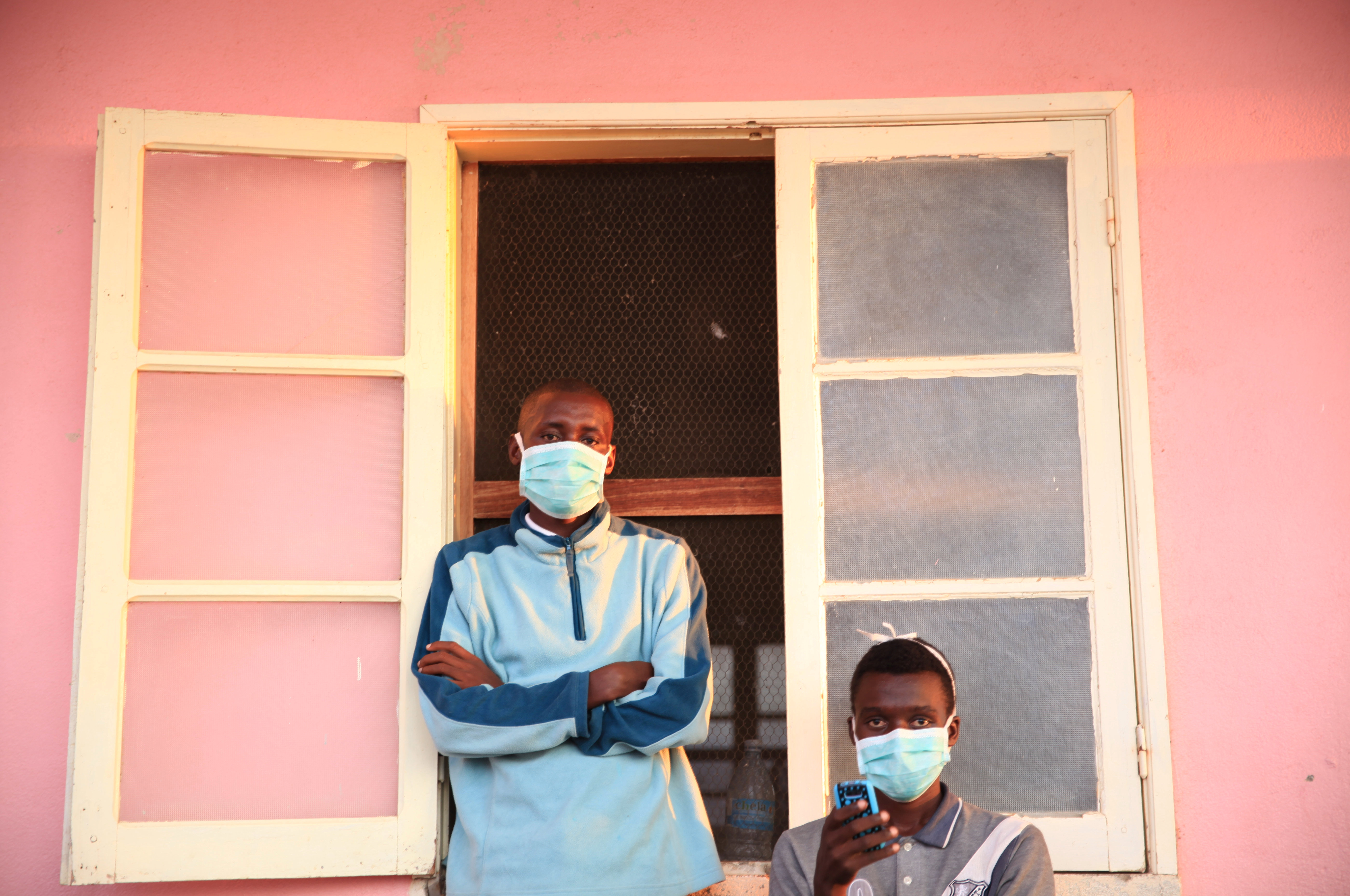Tuberculosis patients, wearing masks to stop the spread of the disease, stand outside their ward at Chiulo Hospital, Cunene province, Angola, Feb. 22, 2018.
