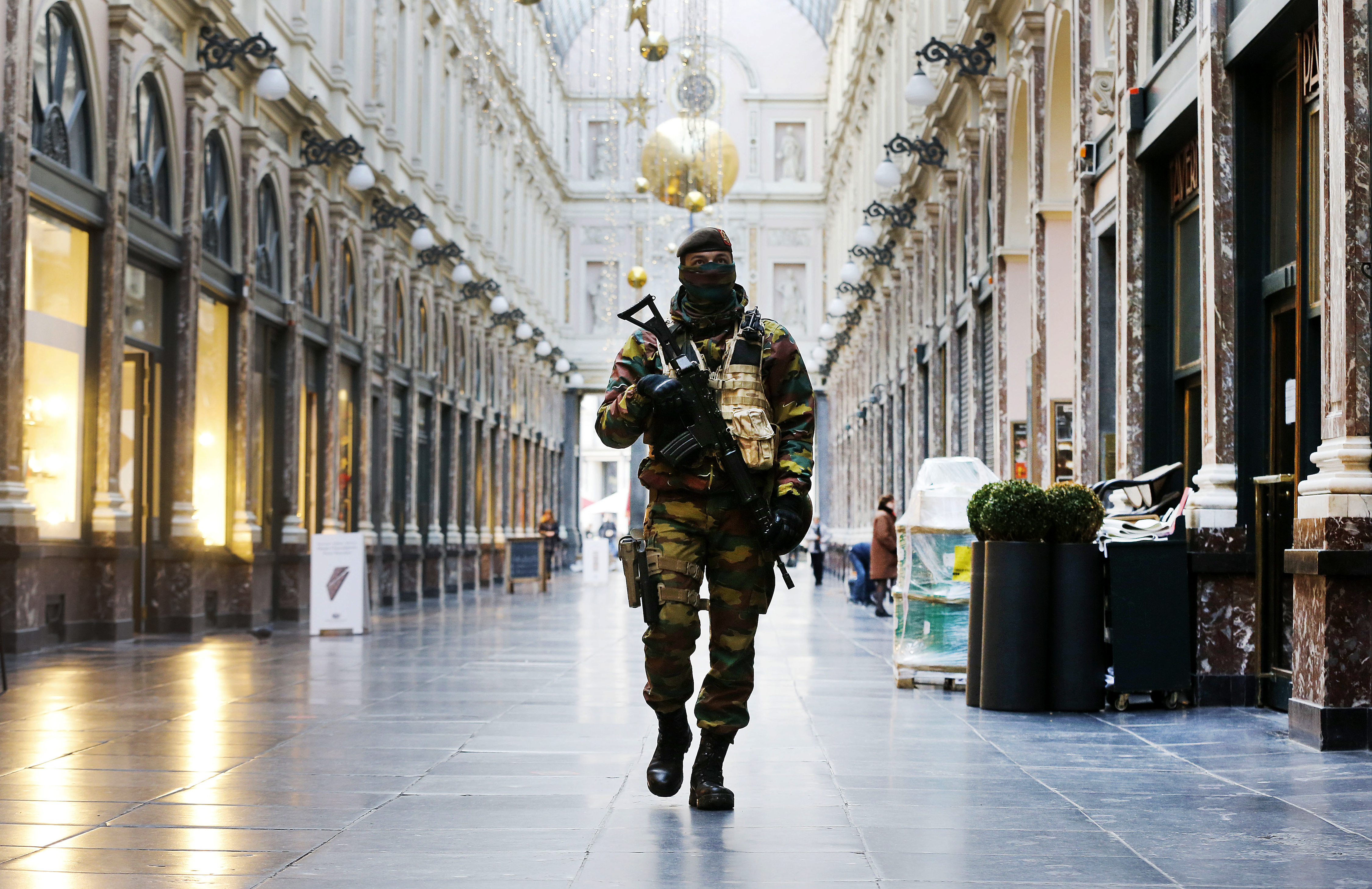 FILE - In this Thursday, Nov. 26, 2015 file photo, a Belgian Army soldier walks through the Galleries Royal Saint-Hubert in the center of Brussels. Some experts say it will take months for Europeans to psychologically adapt to life after the Paris at