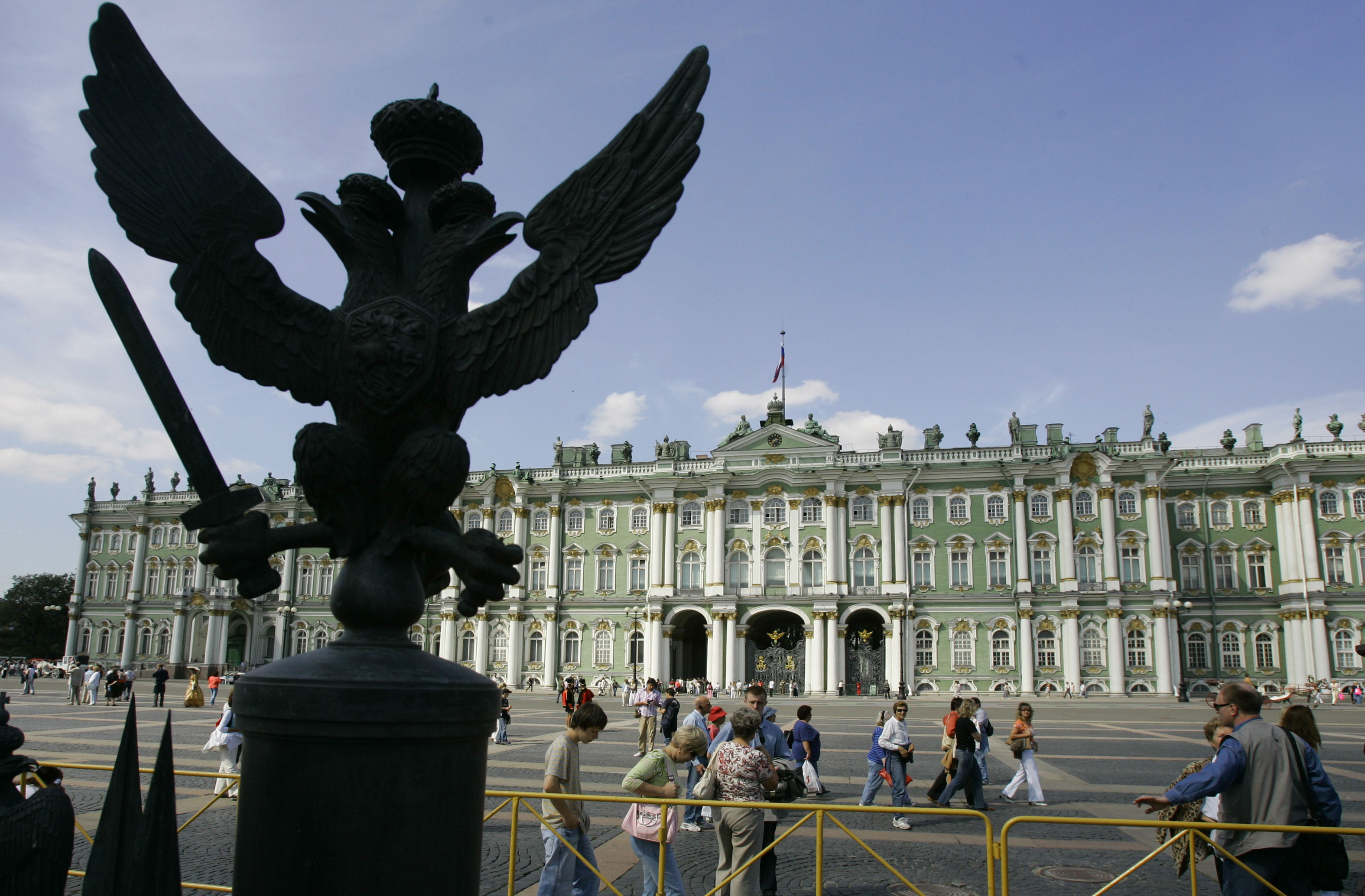 ** FILE ** People make their way past the Winter Palace, the main building of Russia's famed State Hermitage Museum, St.Petersburg, Russia, Aug. 1, 2006, with a sculpture of double-headed eagle, Russia's State Emblem, in the foreground. Hermitage Mus...