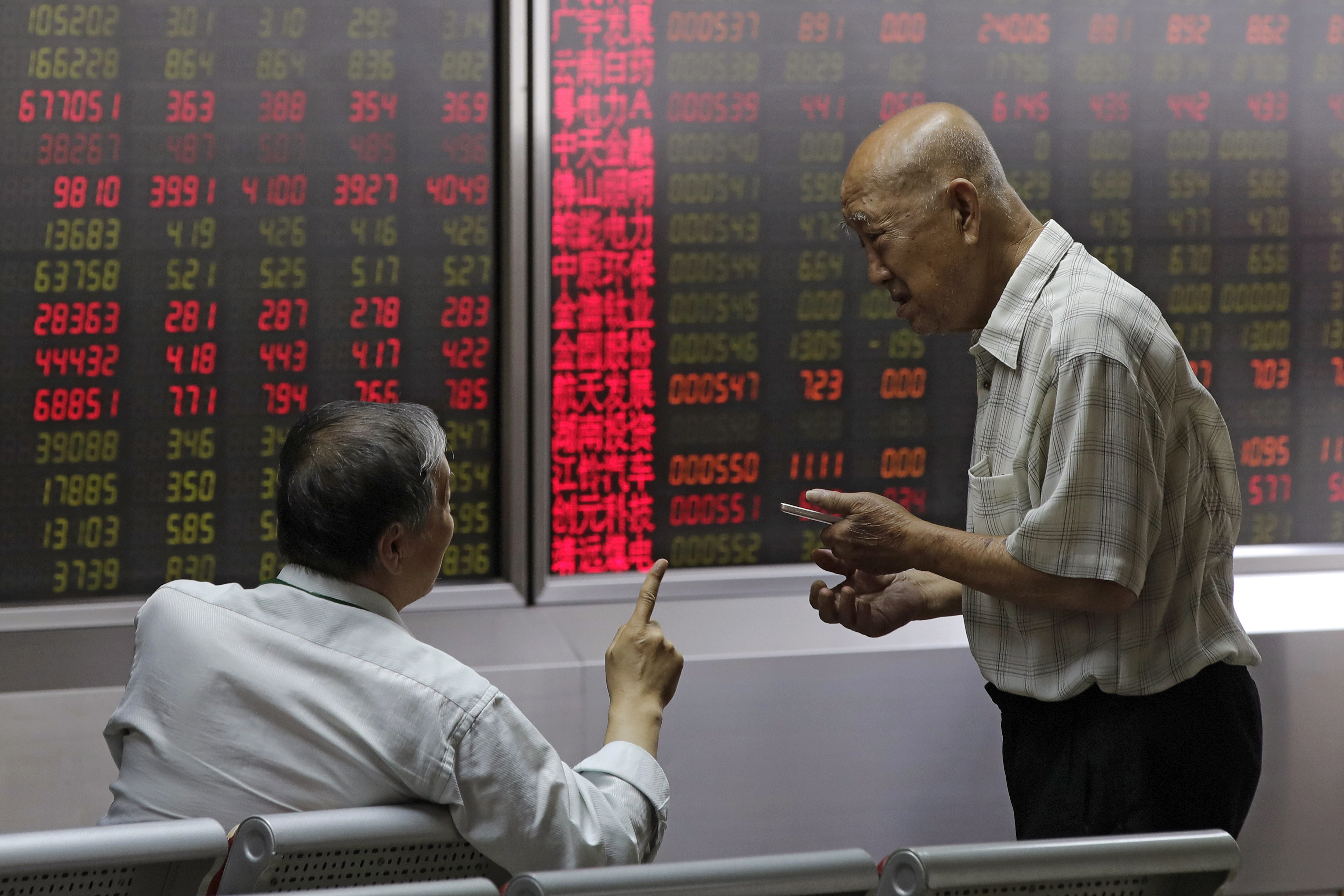 People chat as they monitor stock prices at a brokerage house in Beijing, Aug. 16, 2018.