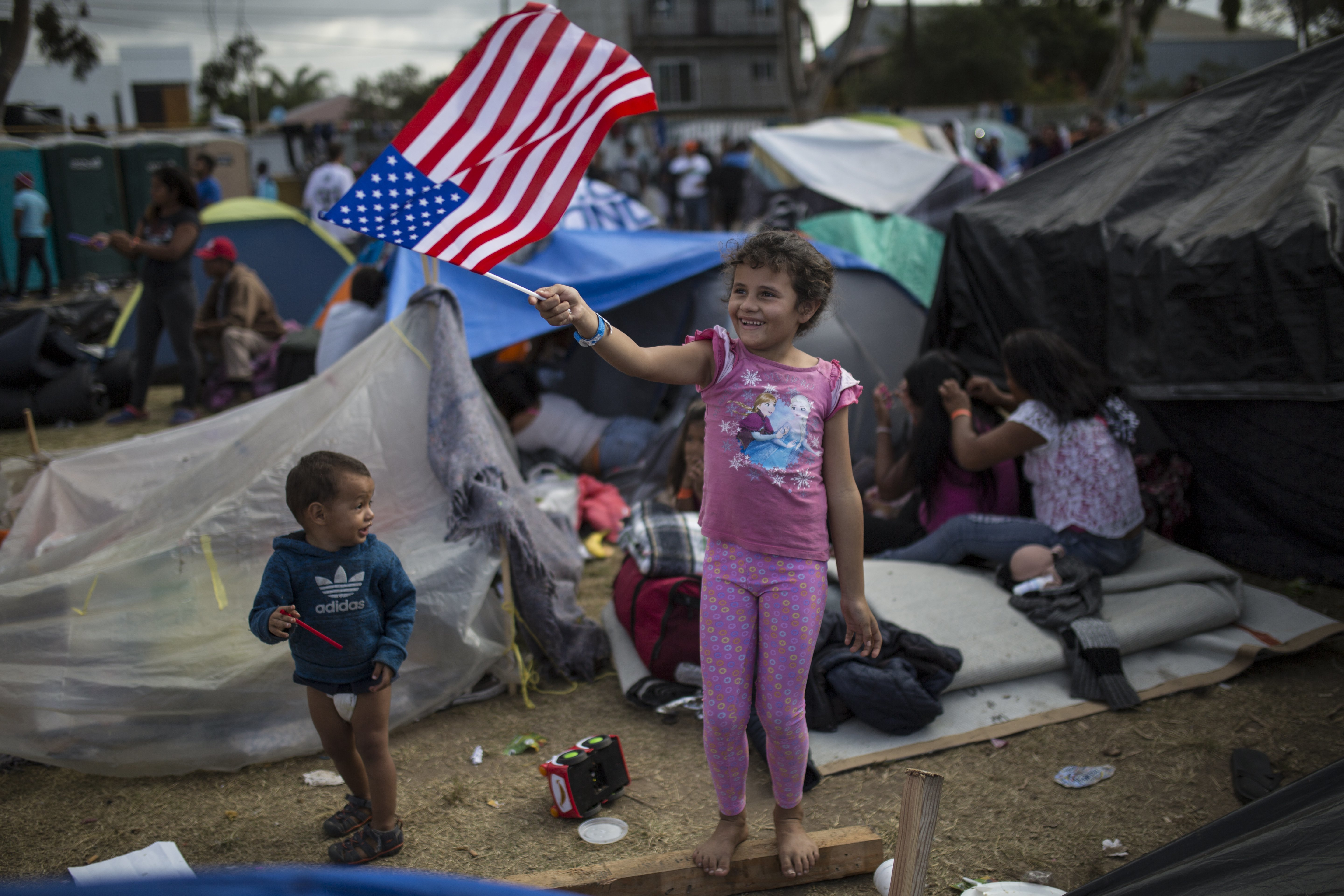 Seven-year-old Honduran migrant Genesis Belen Mejia Flores waves an American flag at U.S. border control helicopters flying overhead near the Benito Juarez Sports Center serving as a temporary shelter for Central American migrants, in Tijuana, Mexico...