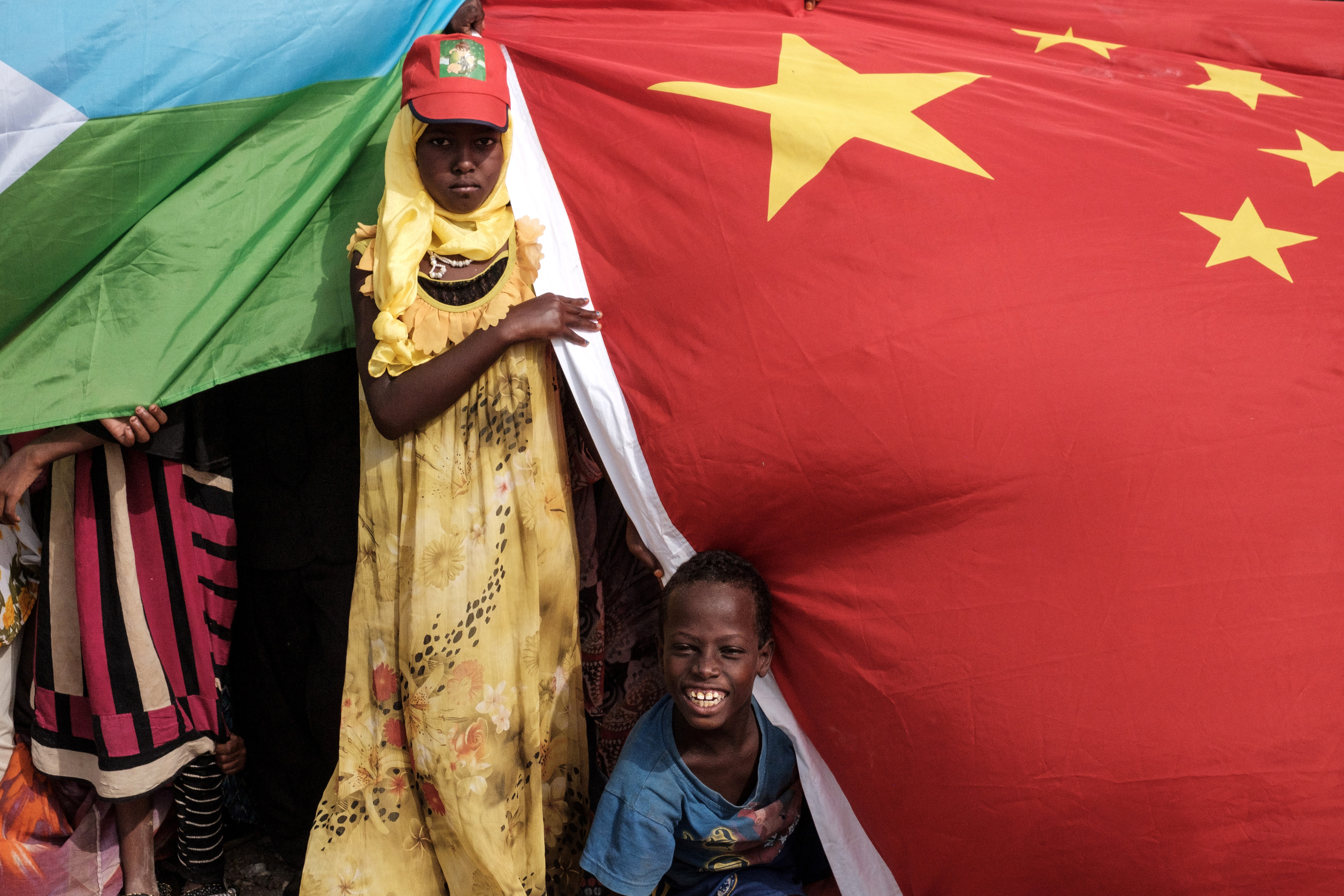 People hold Chinese and Djiboutian national flags as they wait for the arrival of Djibouti's President Ismail Omar Guellehas before the launching ceremony of new 1,000-unit housing construction project in Djibouti, July 4, 2018. The project is financ...
