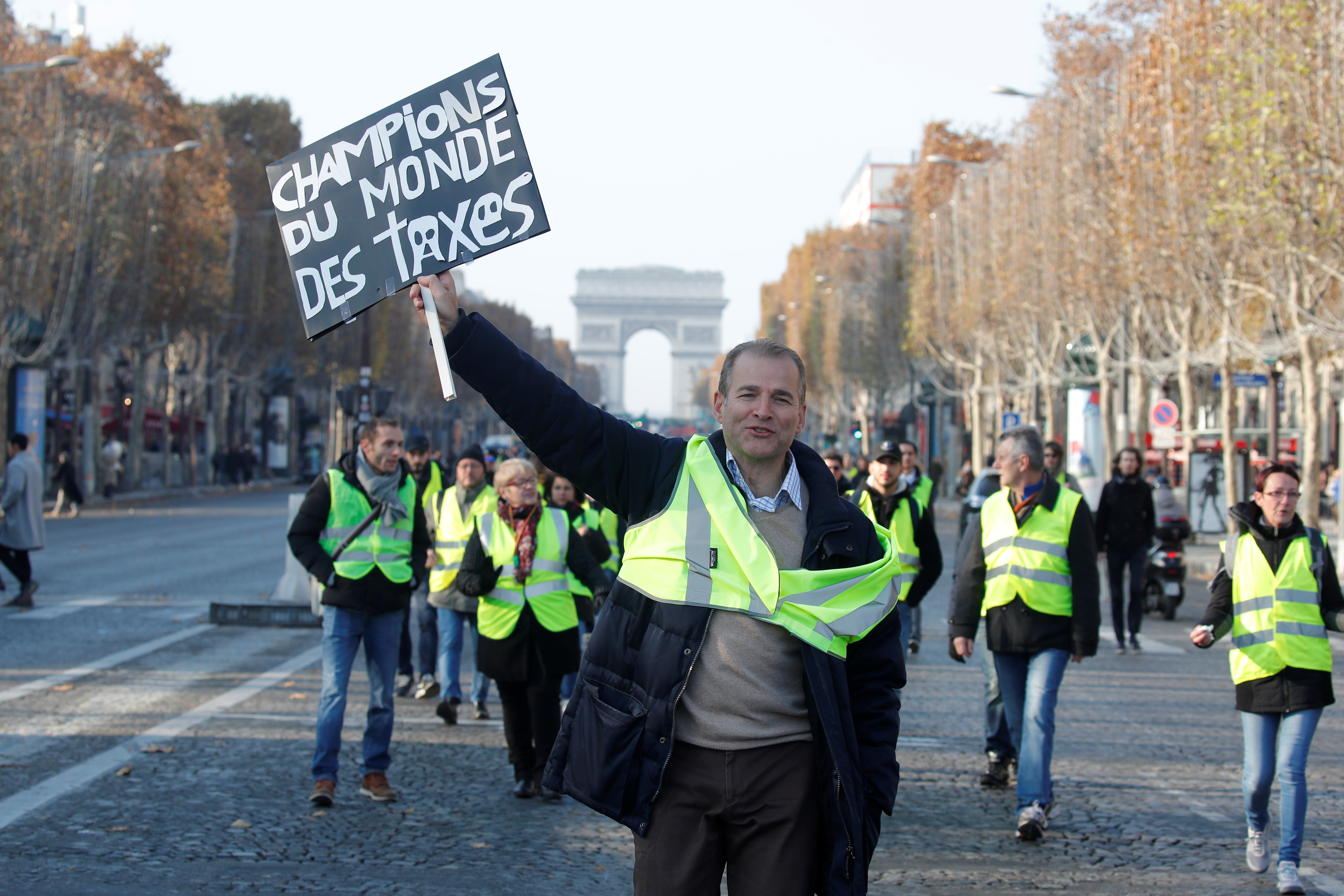 "A man wearing a yellow vest, a symbol of French drivers' protest against higher fuel prices, holds a placard with the message, ""World Champions in Taxes"", as demonstrators gather on the Champs Elysees in Paris, France, Nov. 17, 2018."