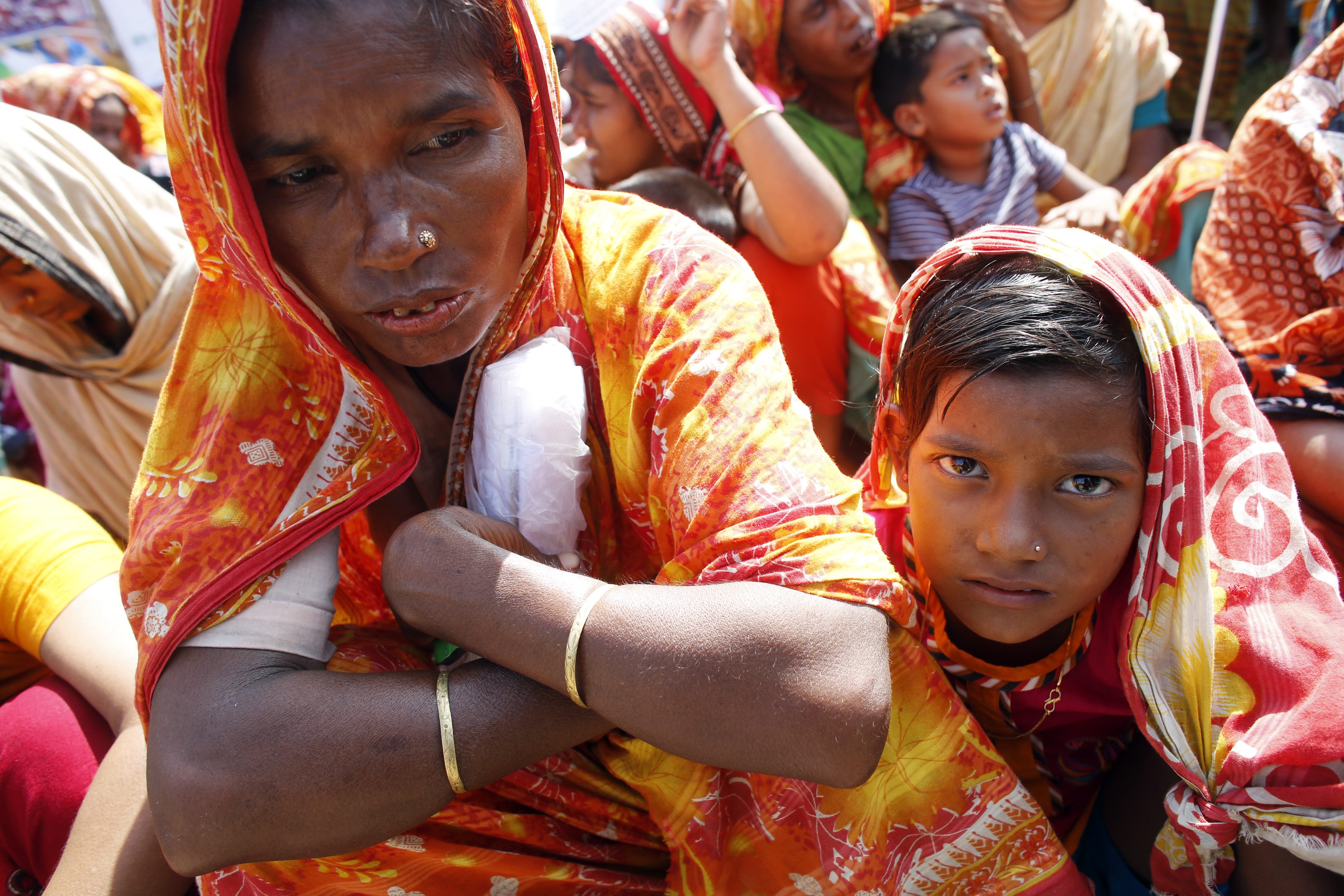A garment worker who survived the Rana Plaza building collapse takes part in a protest with her child to demand compensation, at the factory site in Savar, Bangladesh, October 24, 2013.