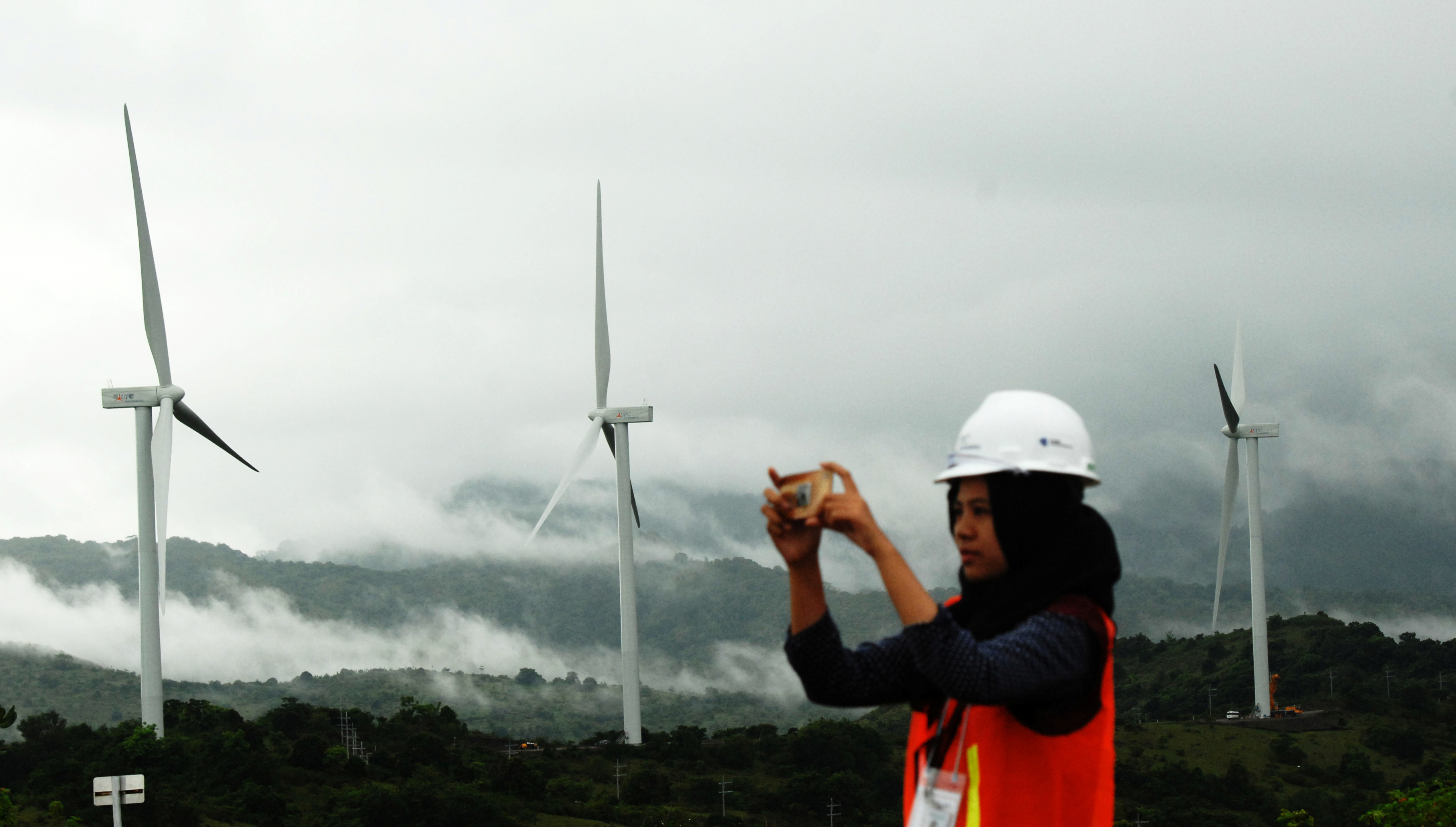 FILE - A woman takes pictures of wind power plant propeller blades in Sidenreng Rappang, Sulawesi Island, Indonesia, Jan. 15, 2018.