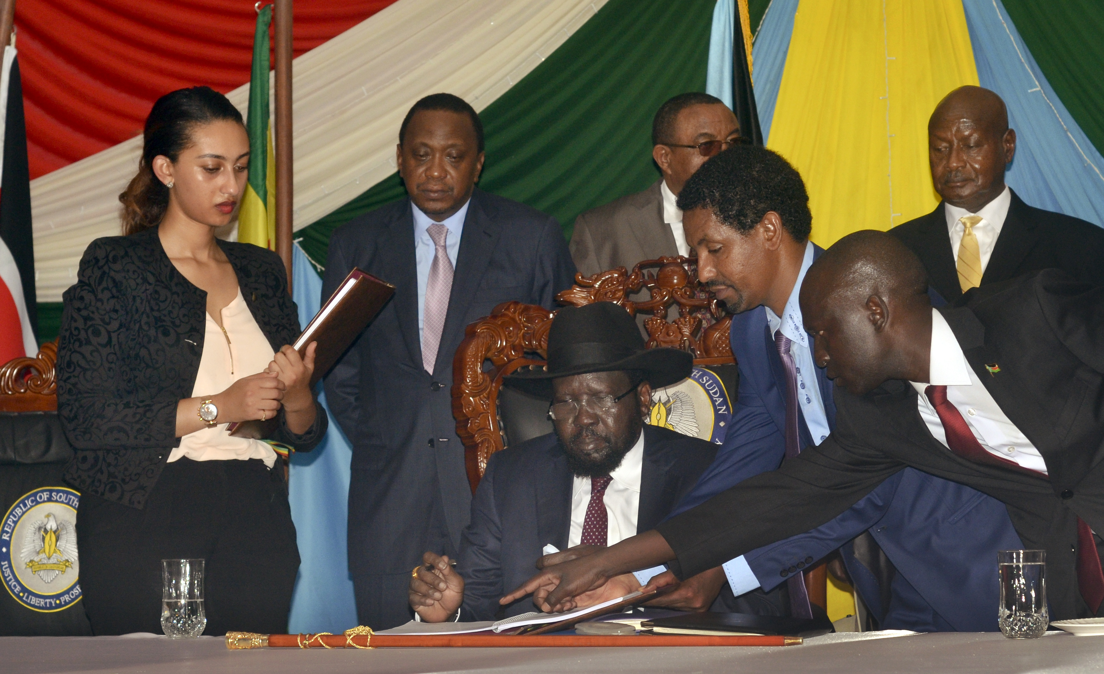 South Sudan President Salva Kiir, seated, signs a peace deal as Kenya's President Uhuru Kenyatta, center-left, Ethiopia's Prime Minister Hailemariam Desalegn, center-right, and Uganda's President Yoweri Museveni, right, look on in Juba, South S...