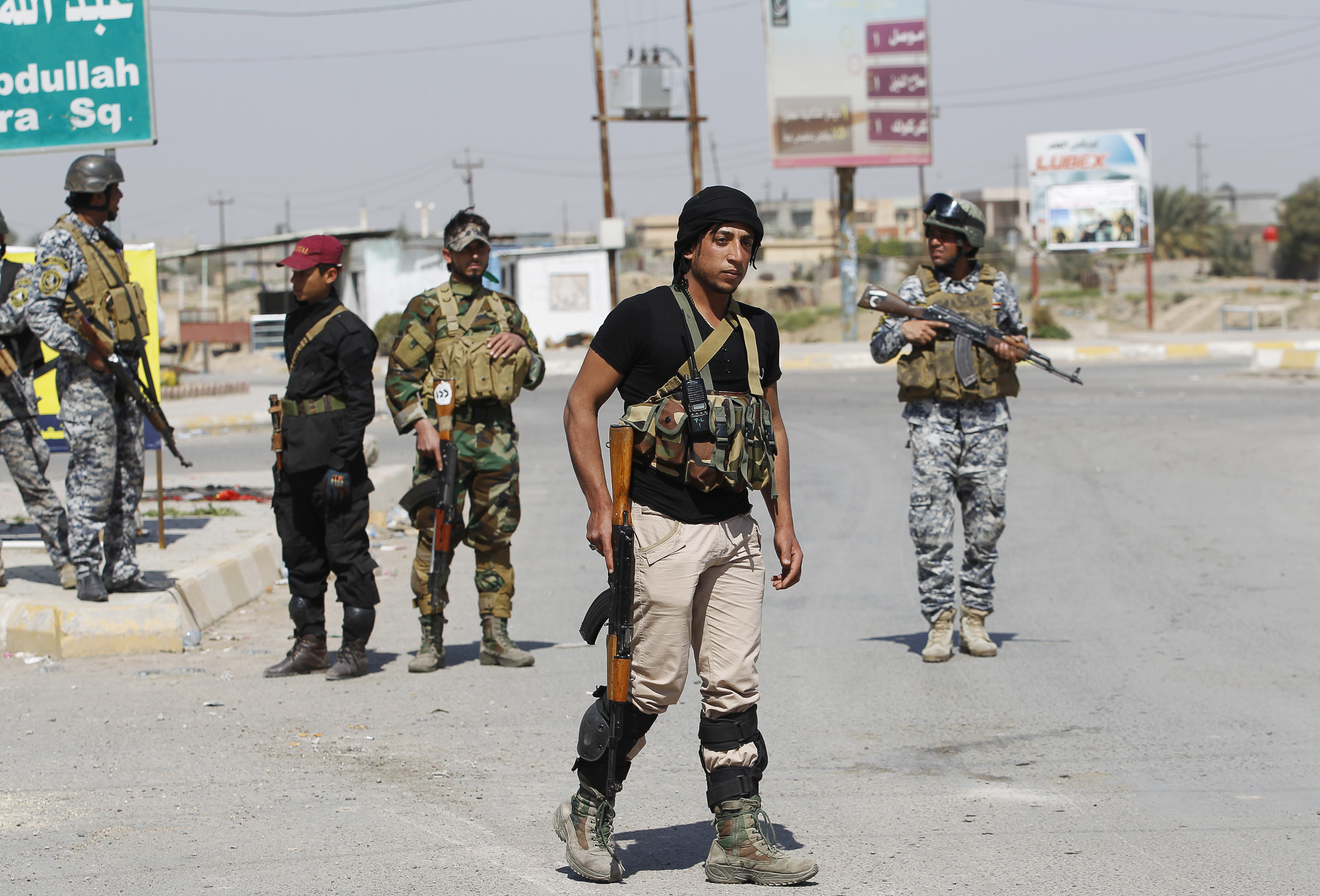 Sunni fighters who have joined Shi'ite militia groups known collectively as Hashid Shaabi (Popular Mobilization), allied with Iraqi forces against the Islamic State group, carry weapons as they stand guard in al-Alam Salahuddin province, March 15, 20...
