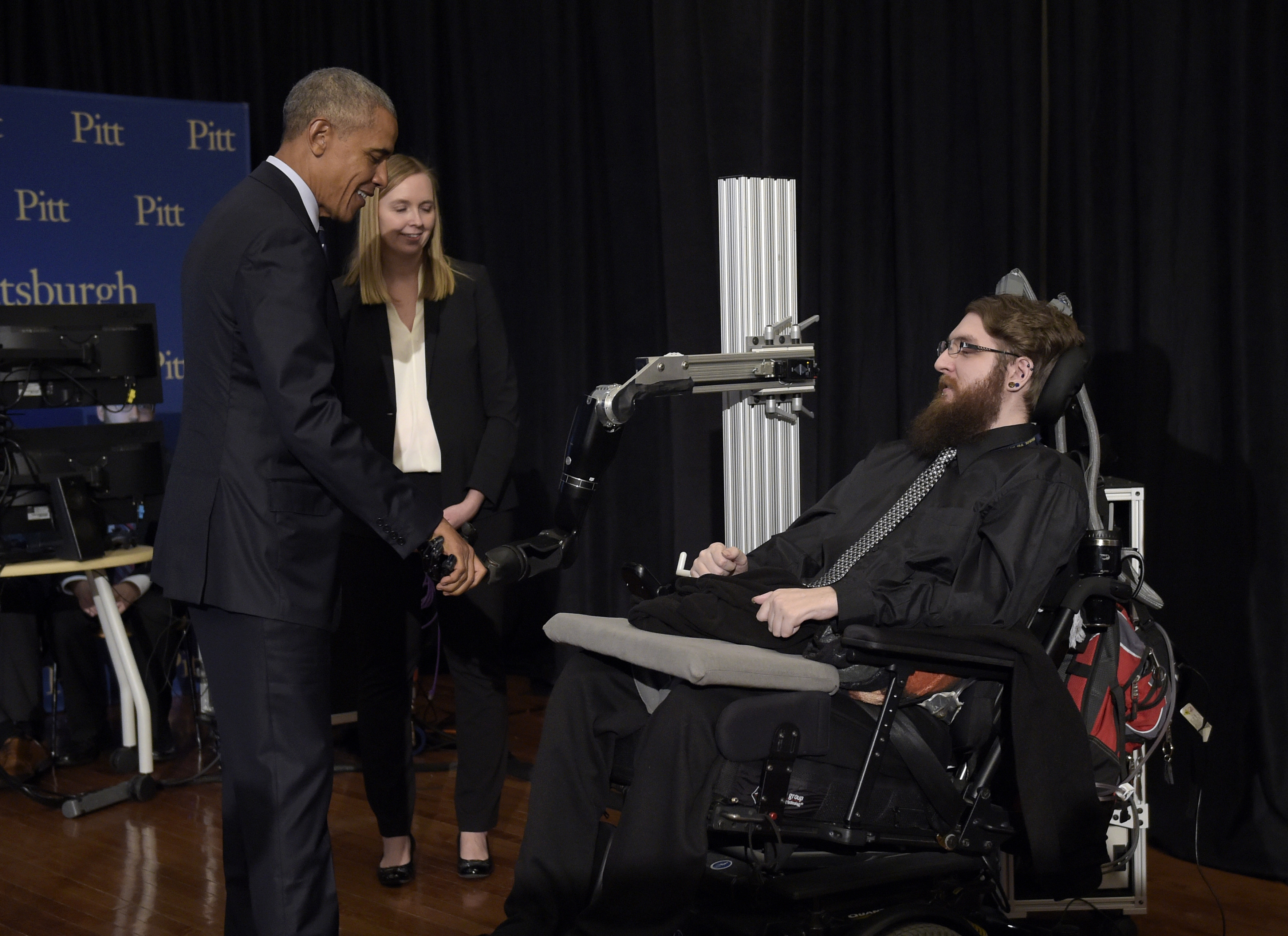 President Barack Obama shakes hands with Nathan Copeland, who demonstrates how he can control a robotic arm and feel when the robotic hand is touched. Dr. Jennifer Collinger, one of Copeland's doctors, watches.
