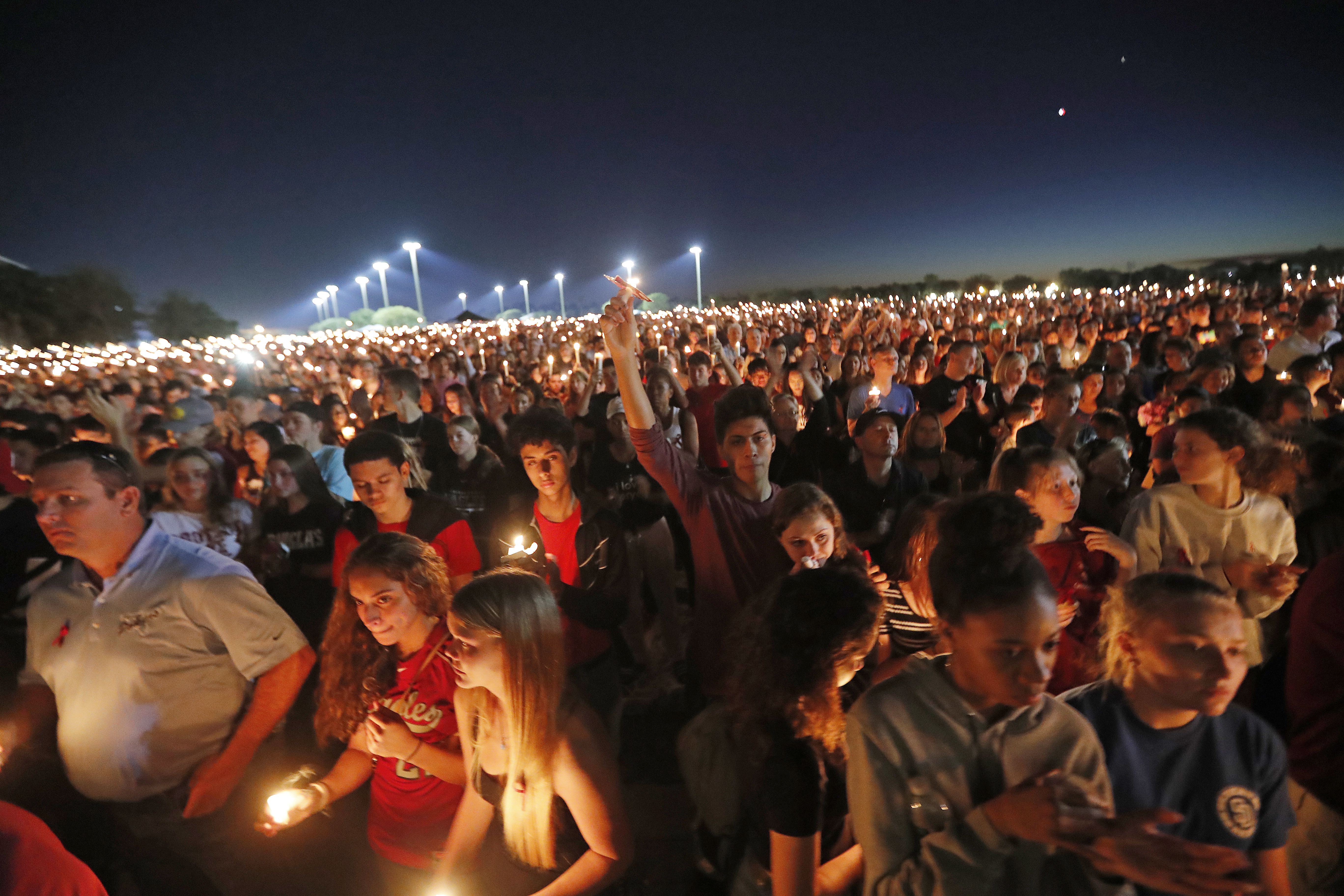 People hoist up their candles during a vigil for the victims of the Wednesday shooting at Marjory Stoneman Douglas High School, in Parkland, Fla., Feb. 15, 2018.