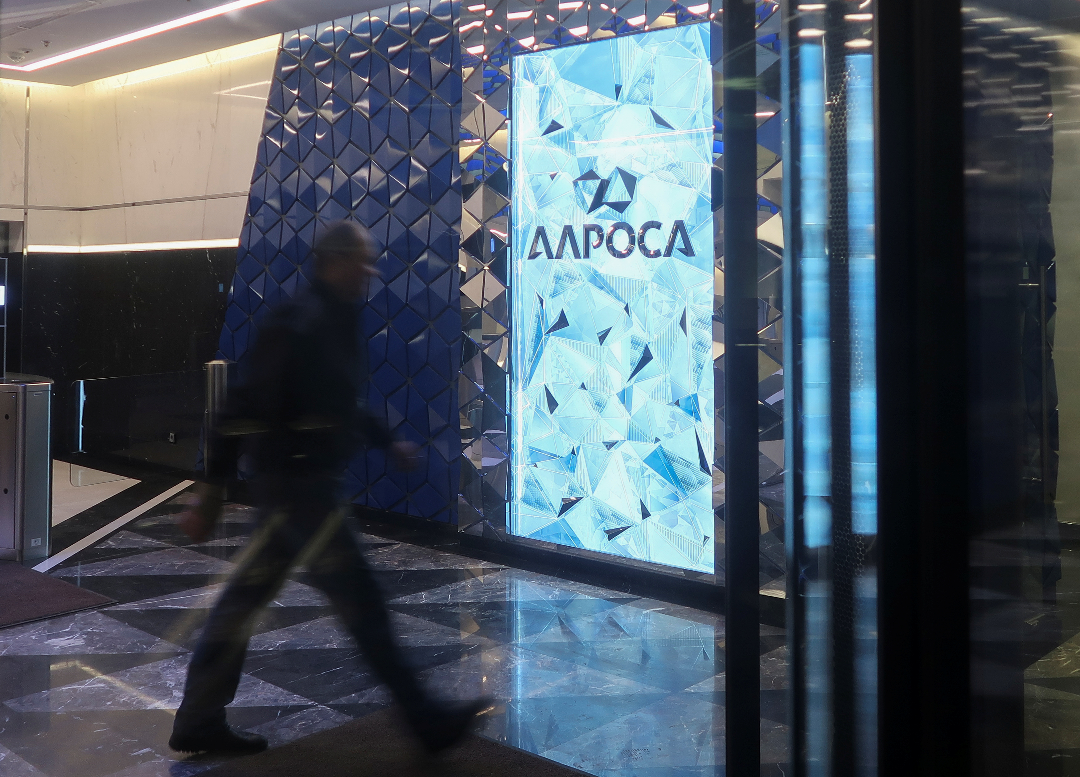 FILE - A man walks past the logo of Russia's diamond producer Alrosa at the entrance of the company's headquarters in Moscow, Russia, Jan. 26, 2018.