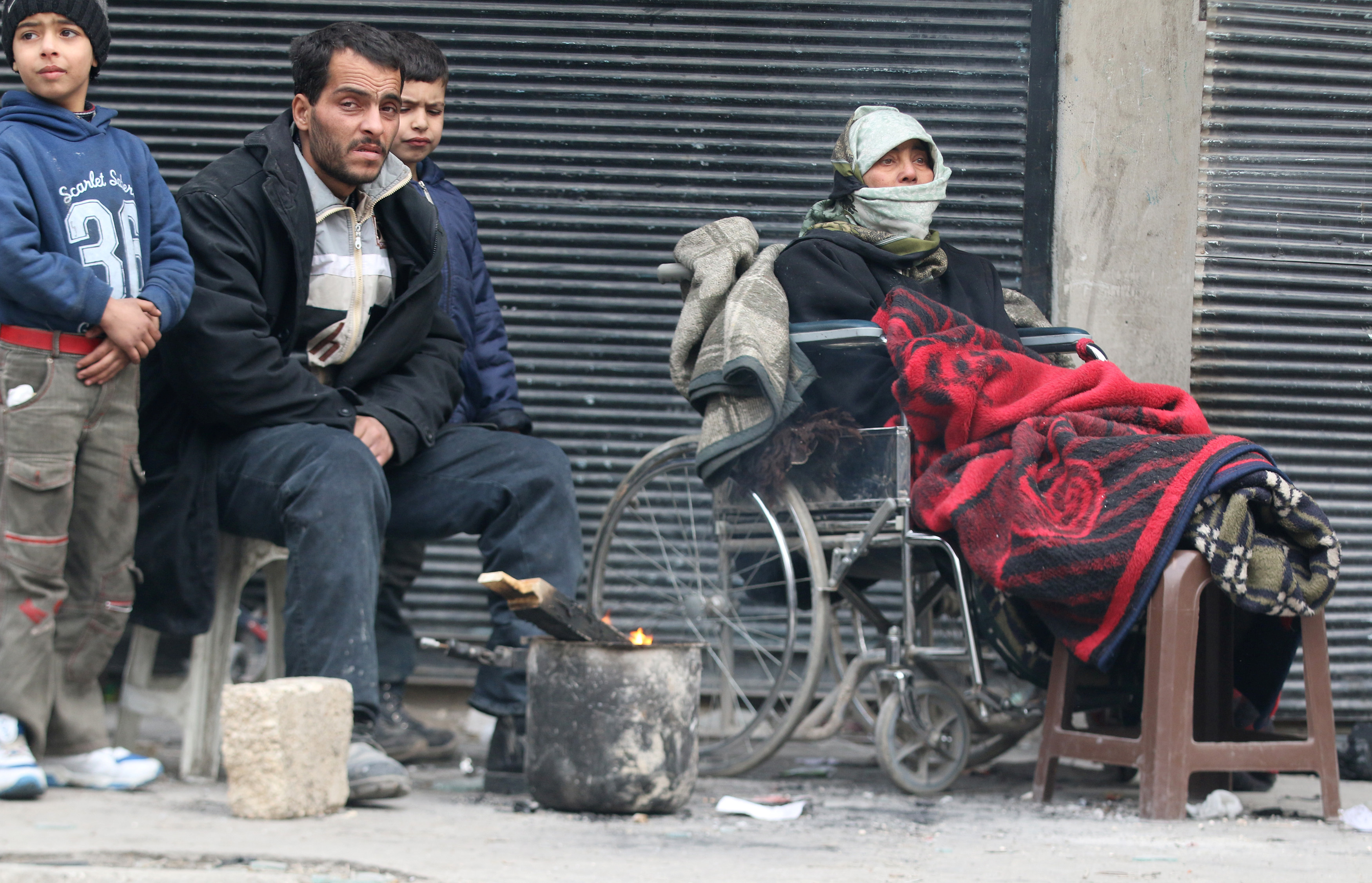 People warm themselves around a fire while waiting to be evacuated from a rebel-held sector of eastern Aleppo, Dec. 17, 2016.