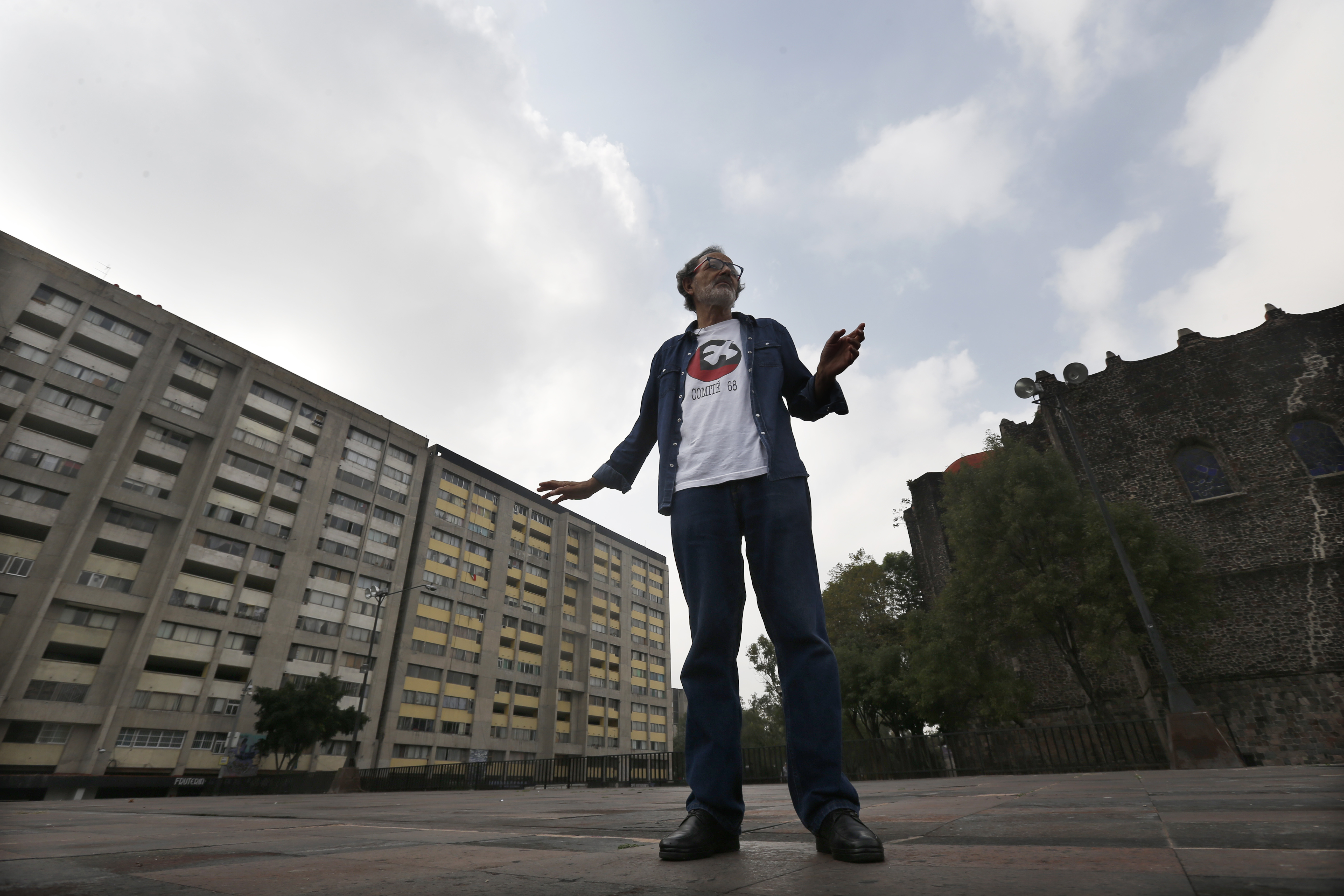 In this Sept. 18, 2018 photo, Enrique Espinosa, who was a medical student when he survived the 1968 Tlateloco massacre, shows the spot where he was when soldiers started shooting in Tlatelolco plaza, Mexico City.