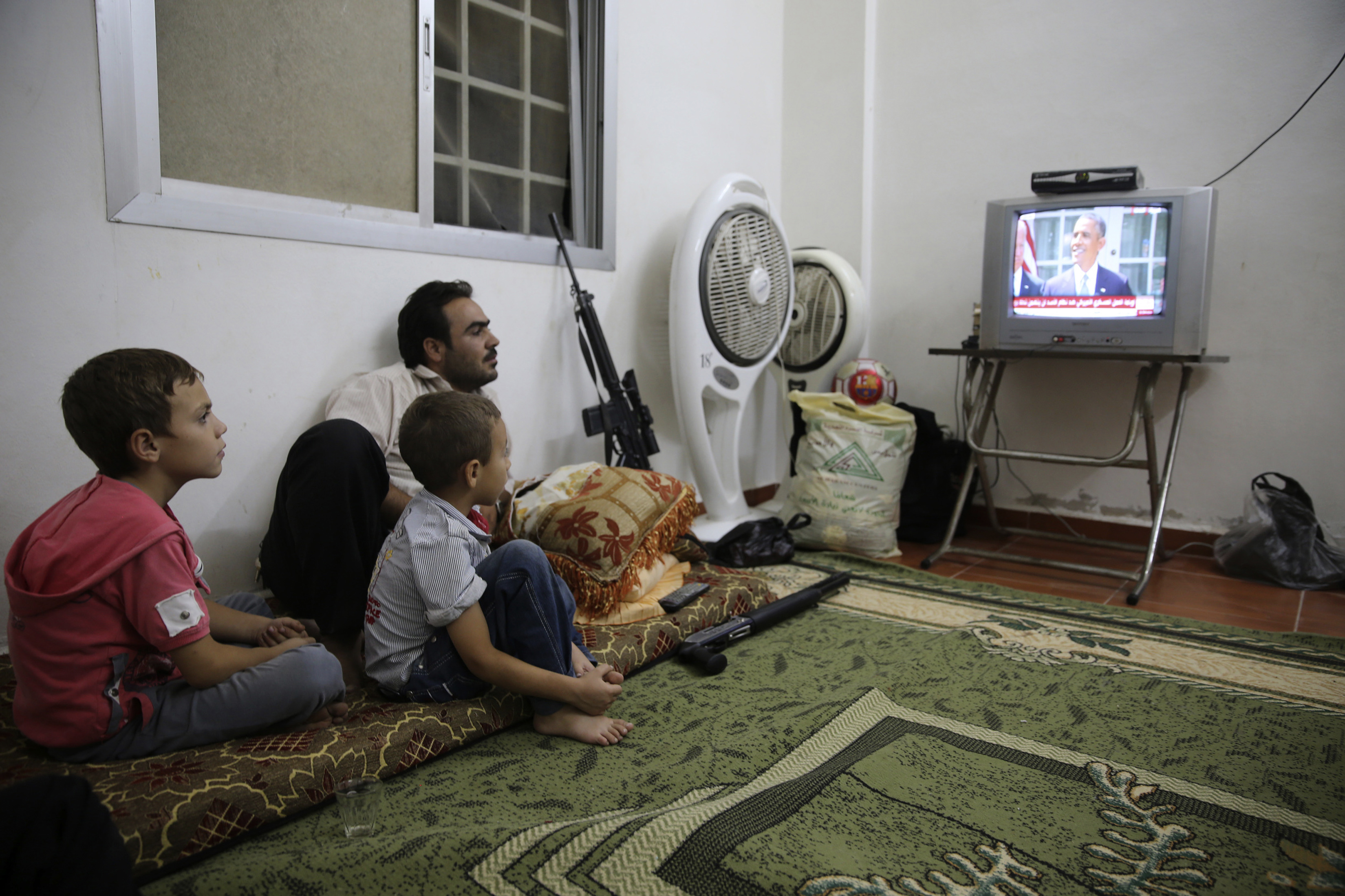 A Free Syrian Army fighter watches U.S. President Barack Obama's speech with his family in Ghouta, Damascus August 31, 2013. Obama on Saturday backed away from an imminent military strike against Syria to seek the approval of the U.S. Congress, in a ...