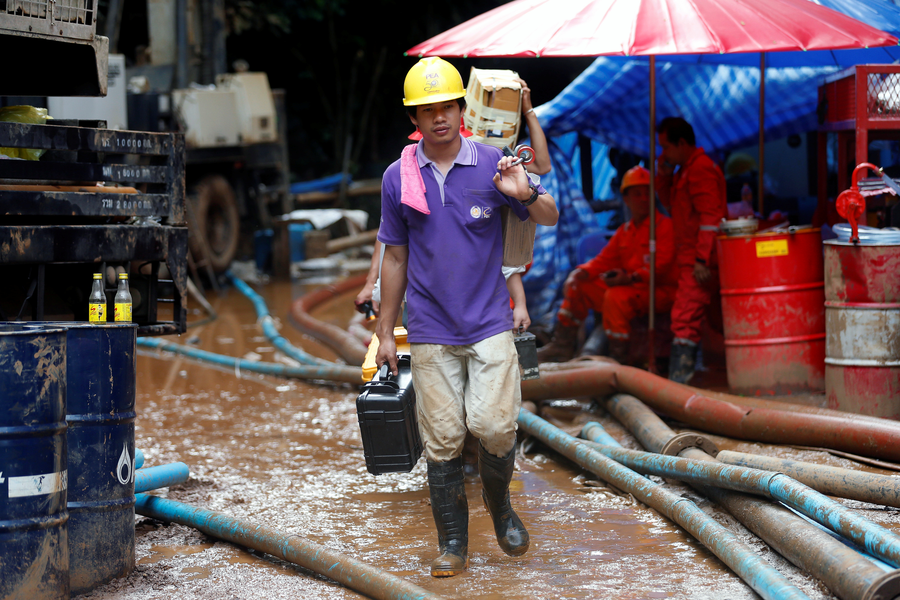 Rescue workers come out from the Tham Luang cave complex in the northern province of Chiang Rai, Thailand, July 3, 2018.