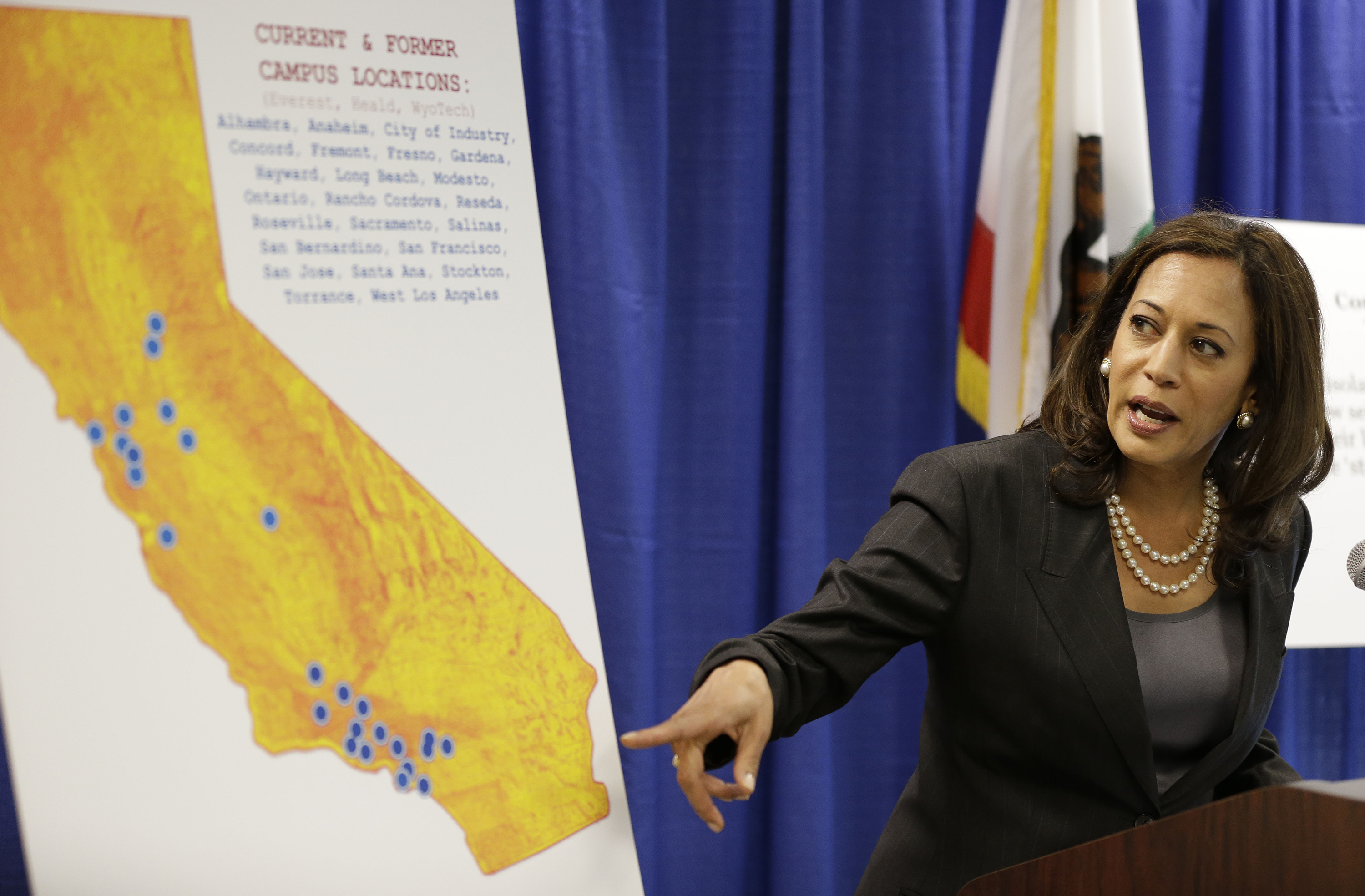 FILE - In this Mar. 24, 2016, file photo, California Attorney General Kamala Harris points to a display showing the location of Corinthian Colleges located in California during a news conference in San Francisco.