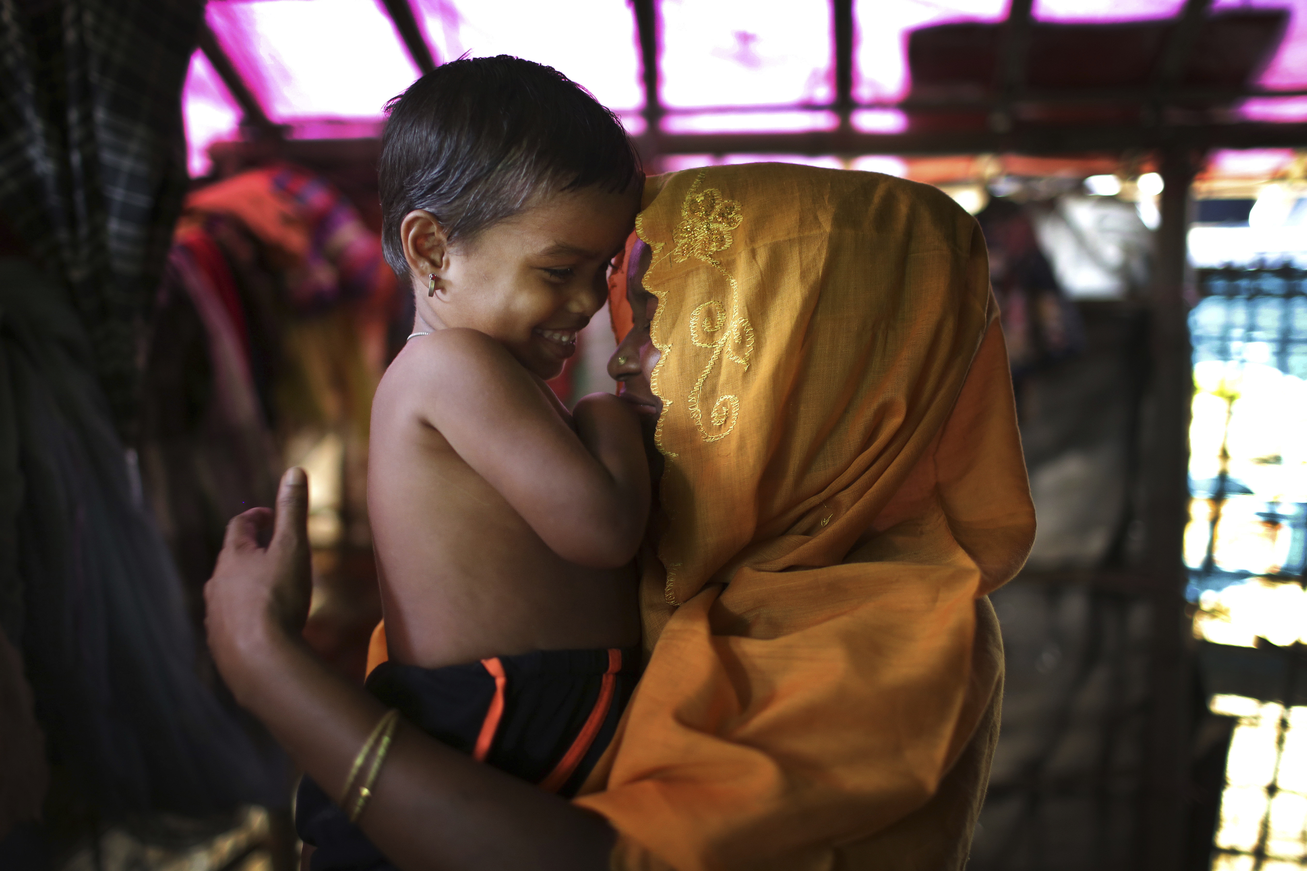 This 28-year-old mother of six, who did not want her name used, says she was raped by members of Myanmar's armed forces in late August. She caresses her daughter while being photographed in her tent in the Kutupalong refugee camp in Bangladesh, Nov. ...