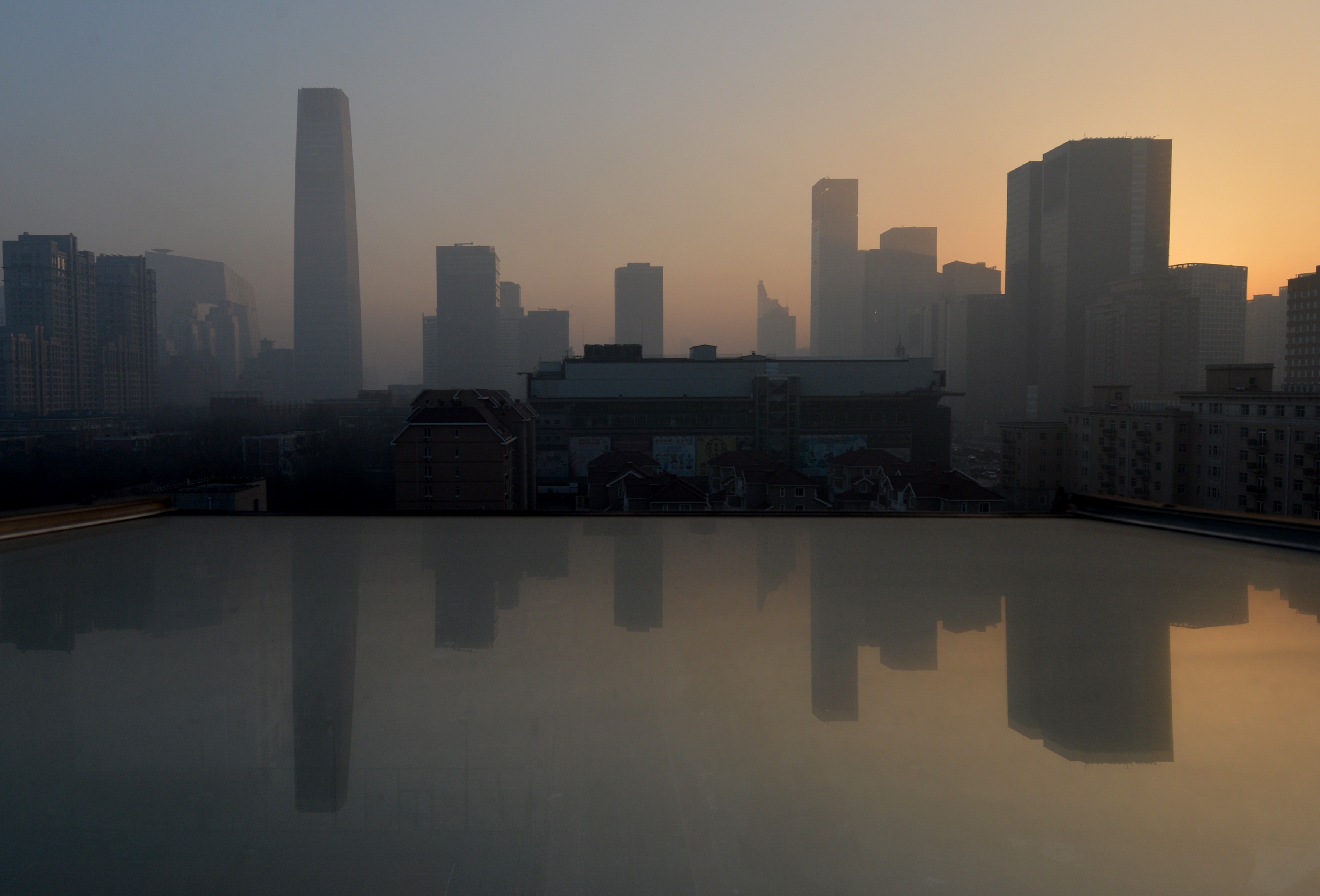 Air pollution hangs over the skyline as the sun rises over Beijing's central business district. Dense smog shrouded the city with pollution at hazardous levels for a fourth day and residents were advised to stay indoors, January 14, 2013.