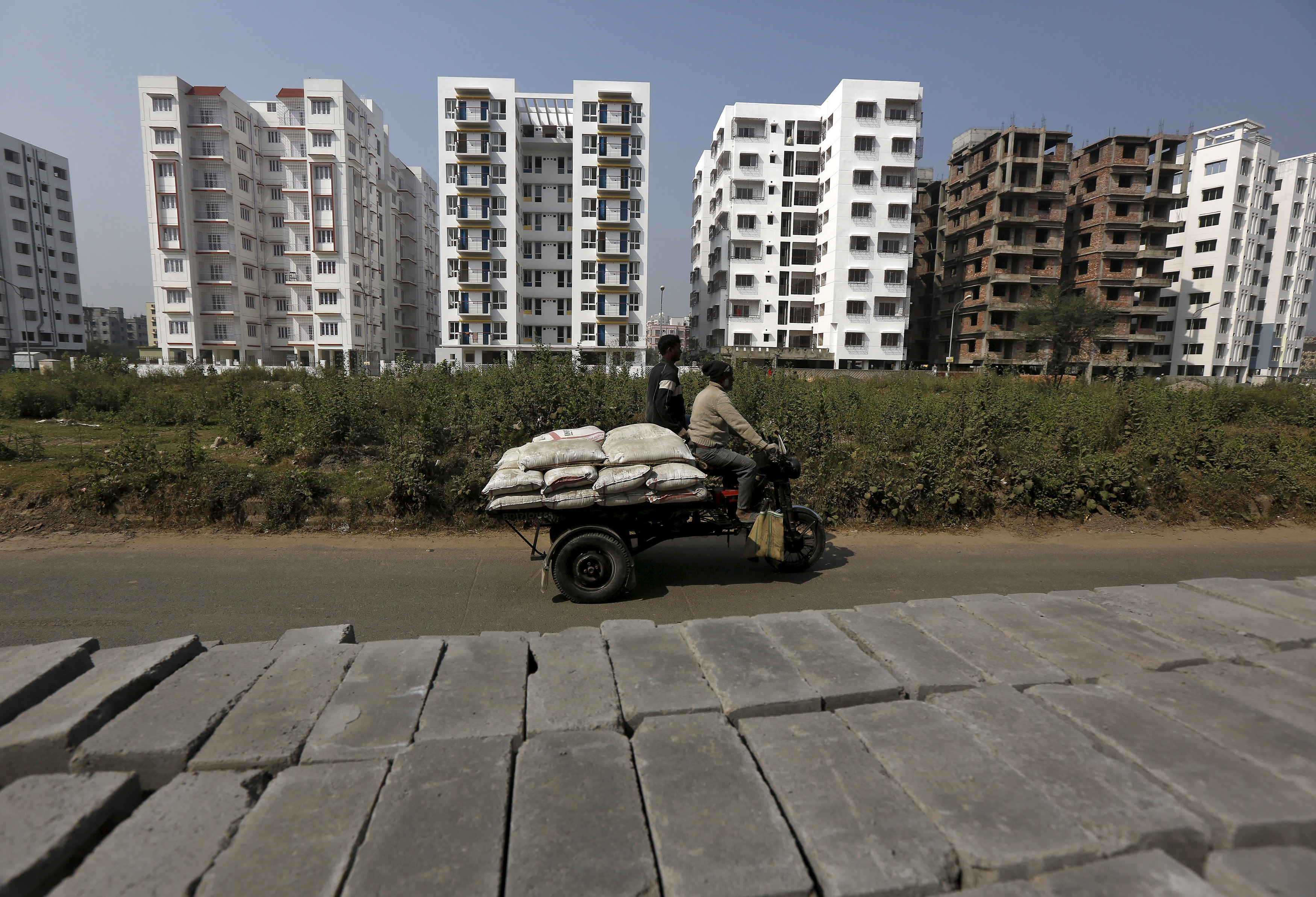 FILE- Laborers transport cement bags onto an improvised motorized rickshaw at the construction site of a residential complex on the outskirts of Kolkata, India, Jan. 23, 2016.