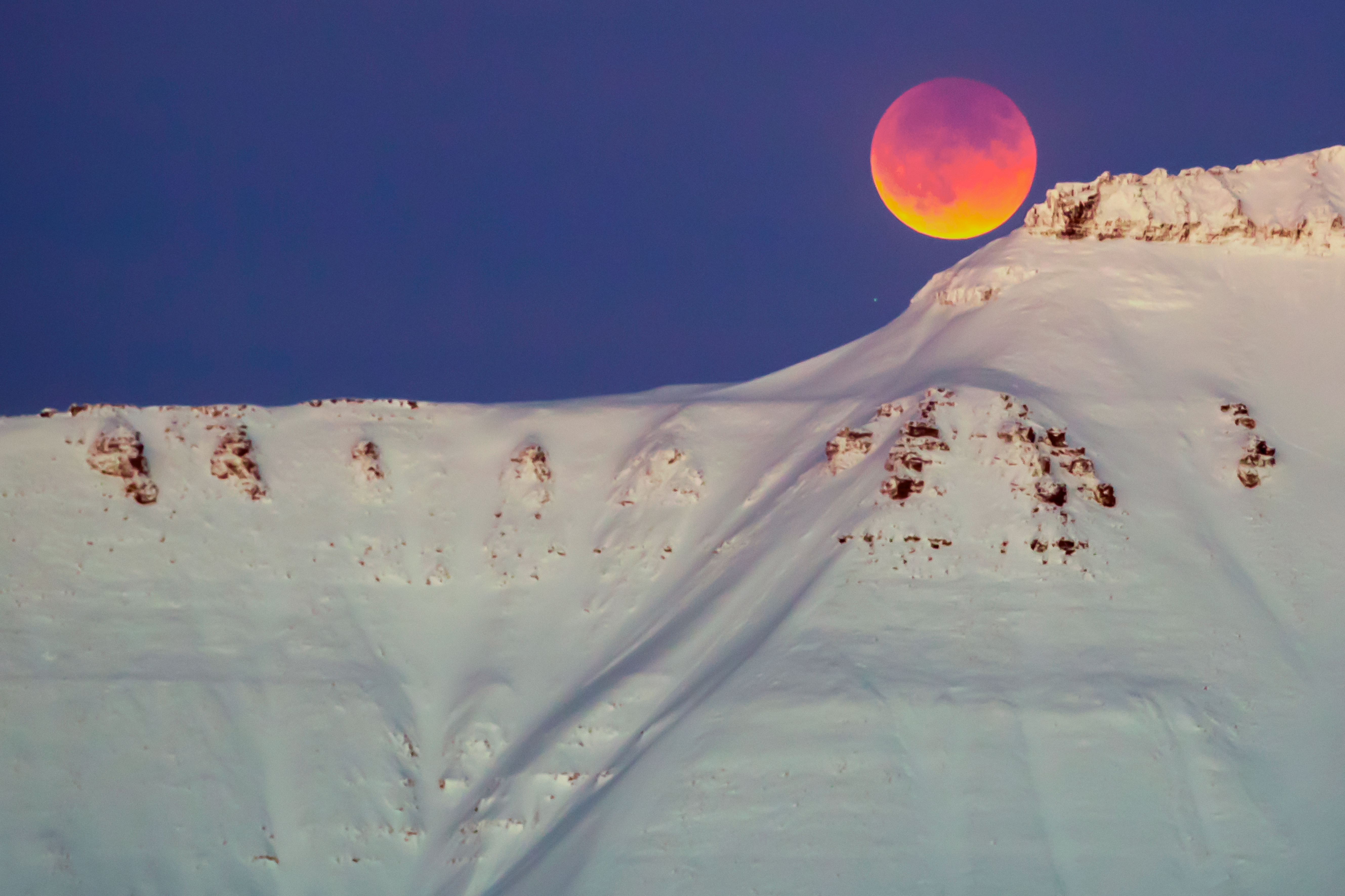 A super blue blood moon behind a mountain is seen from Longyearbyen, Svalbard, Norway, on January 31, 2018.