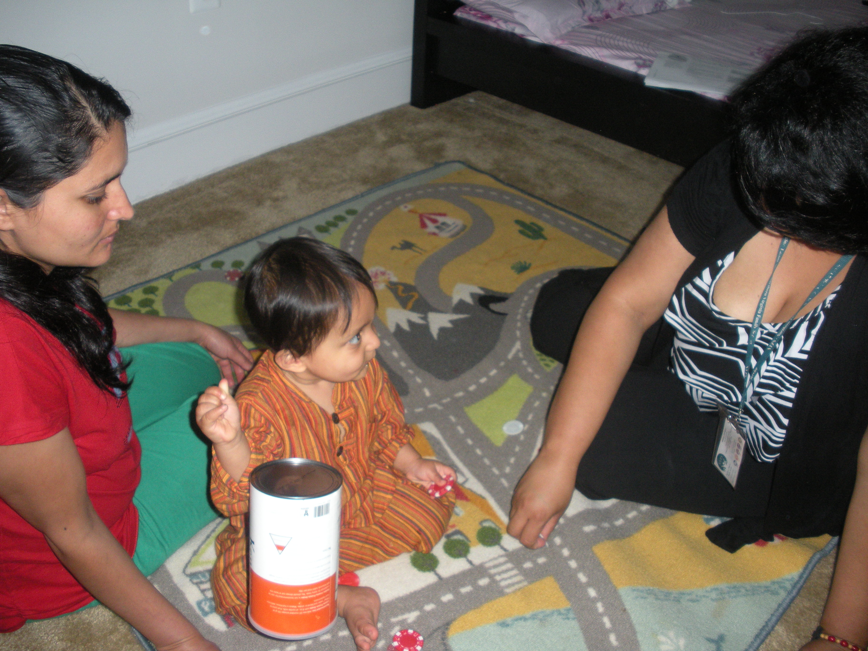 With Vijan's mother Bhawana looking on, family support worker Tina Fontaine uses play time to help develop the baby's motor skills. (VOA/J. Taboh)