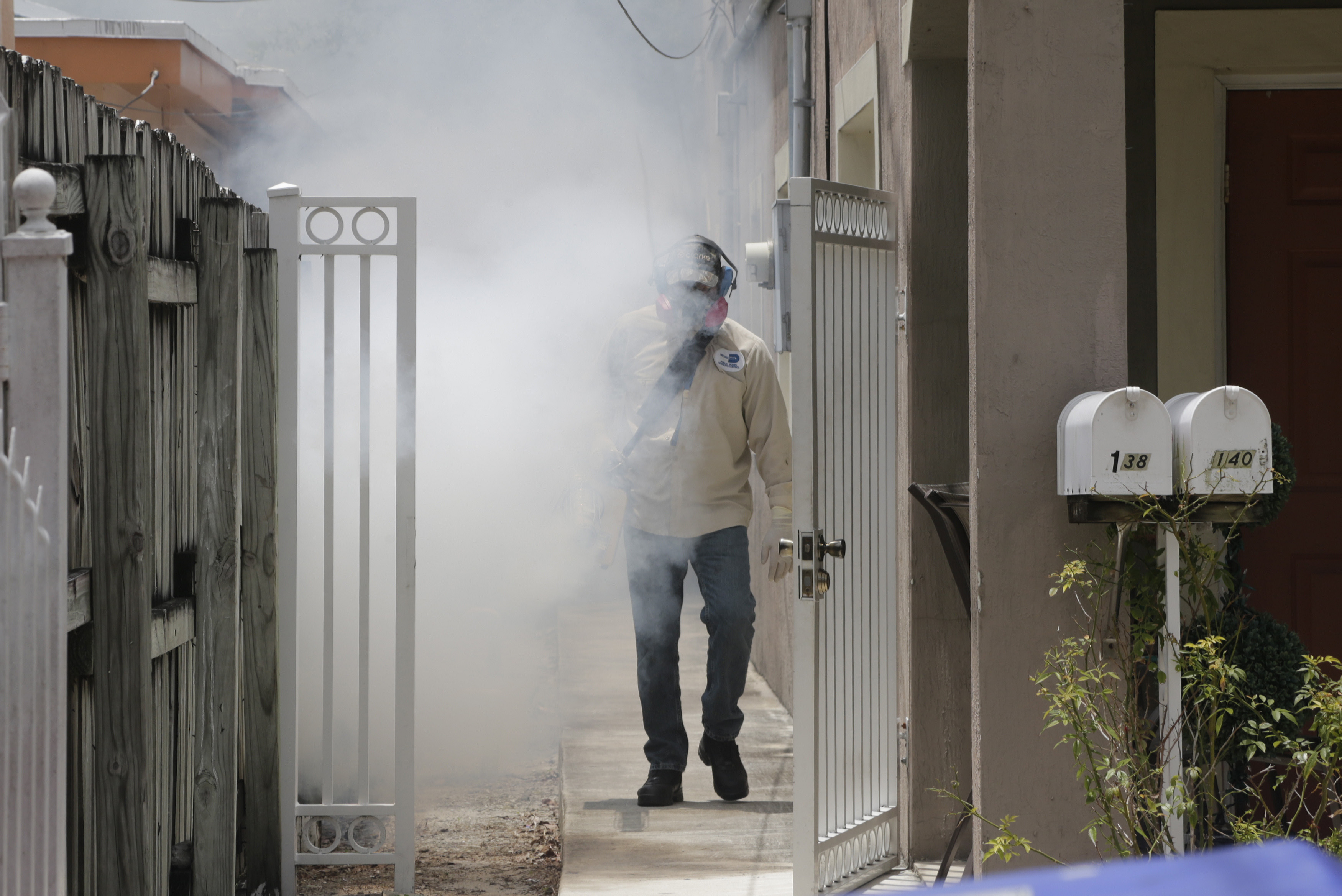 A Miami-Dade County mosquito control worker sprays around a home in the Wynwood area of Miami, Aug. 1, 2016.