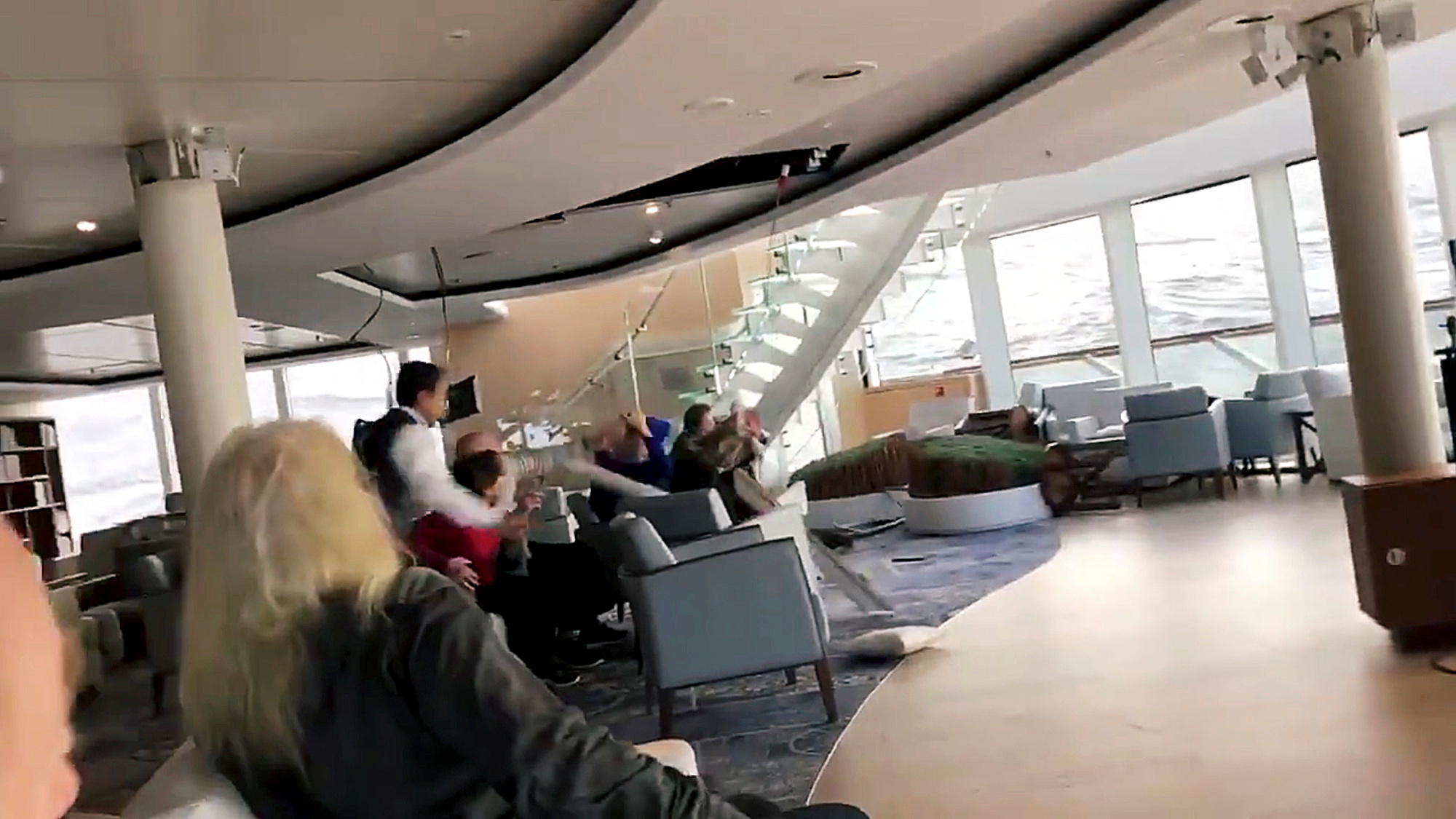 Passengers protect themselves from a collapsing ceiling aboard the cruise ship Viking Sky while listed, after an engine failure, near Hustadvika, Norway, March 23, 2019, in this still image obtained from a social media video.