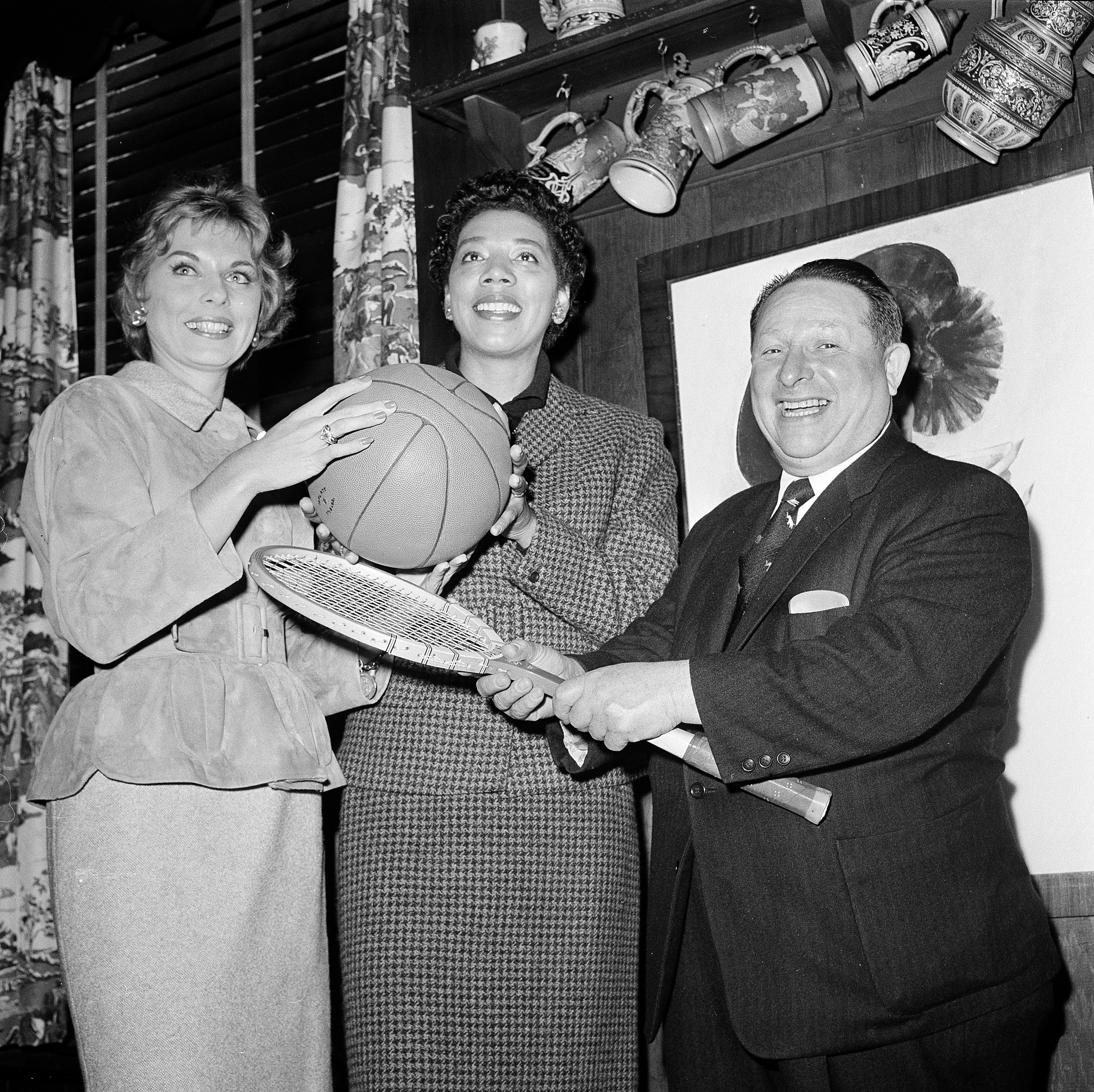 Tennis stars Althea Gibson, center, and Karol Fagerol are shown with Harlem Globetrotters' owner Abe Saperstein, where the women signed a professional contract with the Globetrotters to play at exhibition matches, Oct. 19, 1959, in New York.  (AP Pho...