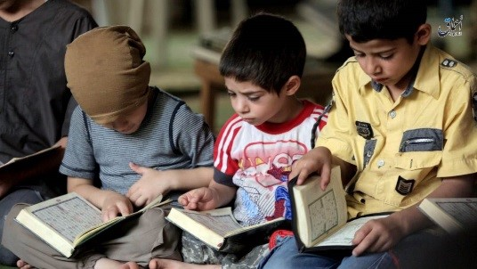 Young boys recite the Quran as part of Islamic State-run school curriculum.