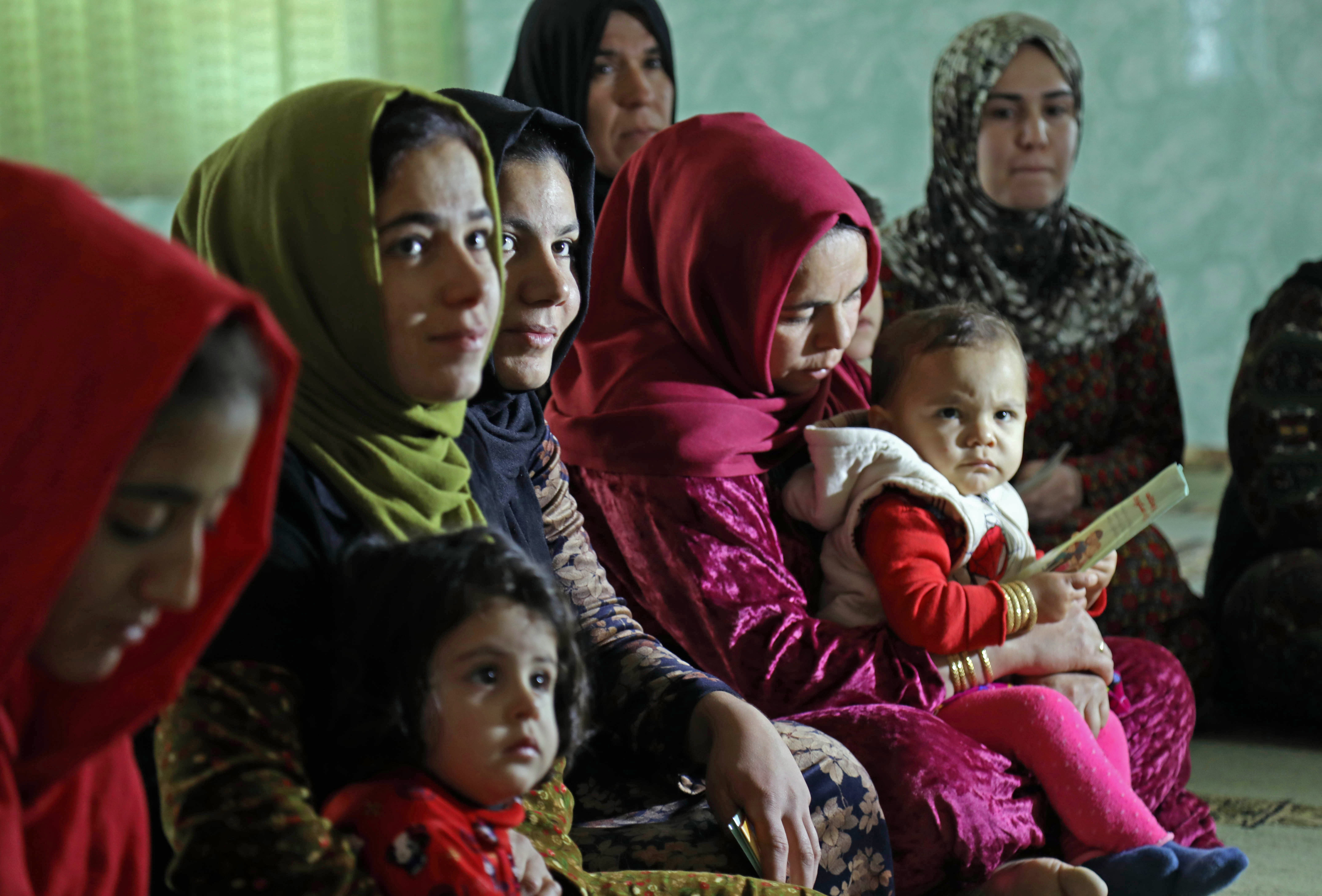 Women and young girls listen to Rasul (not pictured), an Iraqi Kurdish activist with the nonprofit organization WADI, as she speaks about the harms of genital mutilation in Sharboty Saghira, Iraq, Dec. 3, 2018.