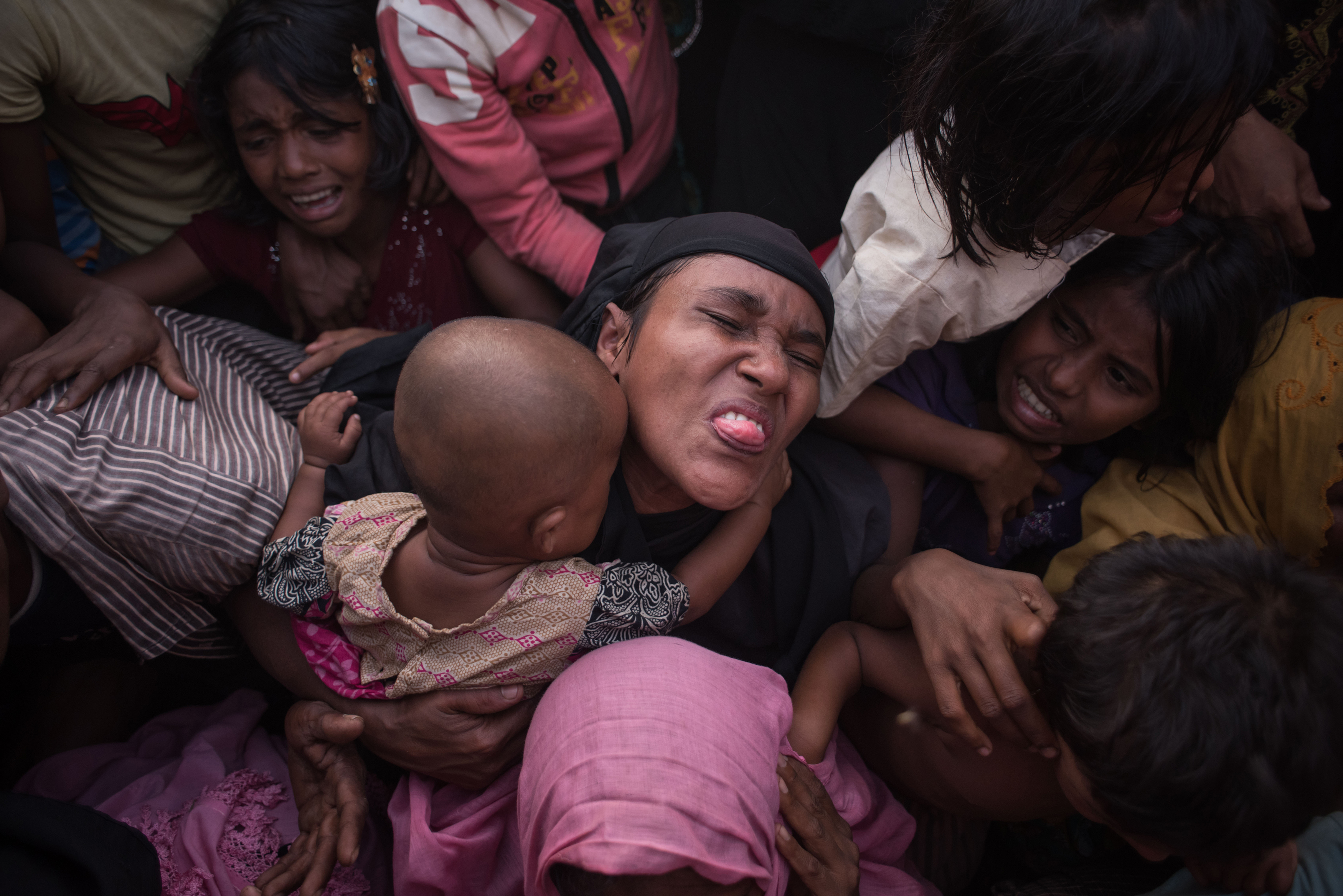 Rohingya Muslim refugees react as police and officials attempt to control a surging crowd as they wait to be called to recieve food aid of rice, water, and cooking oil in a relief centre at the Kutupalong refugee camp in Cox's Bazar on November 28, 2...