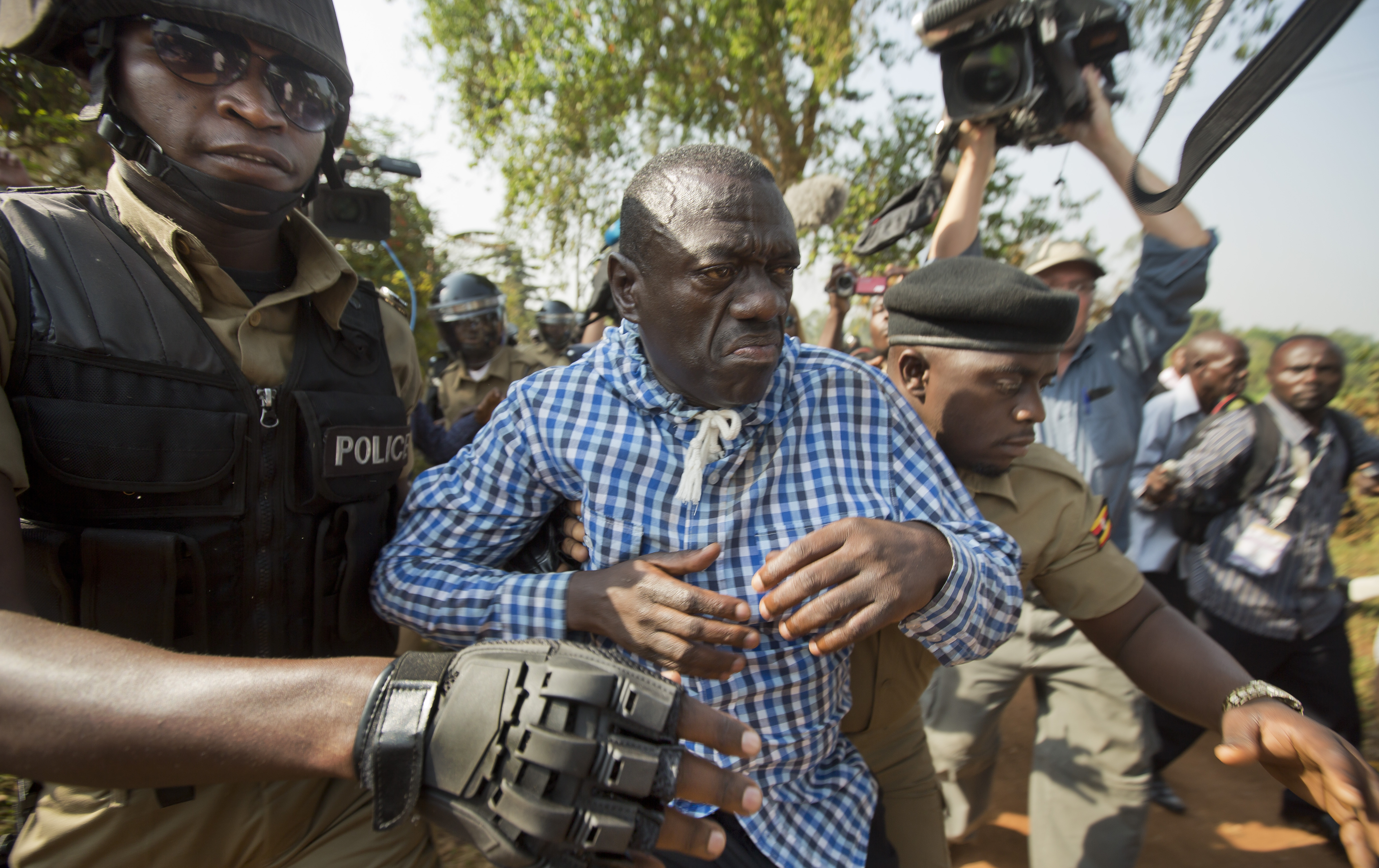Uganda's main opposition leader Kizza Besigye, center, is arrested by police and thrown into the back of a blacked-out police van which whisked him away and was later seen at a rural police station, outside his home in Kasangati, Uganda, Feb. 22, 201...