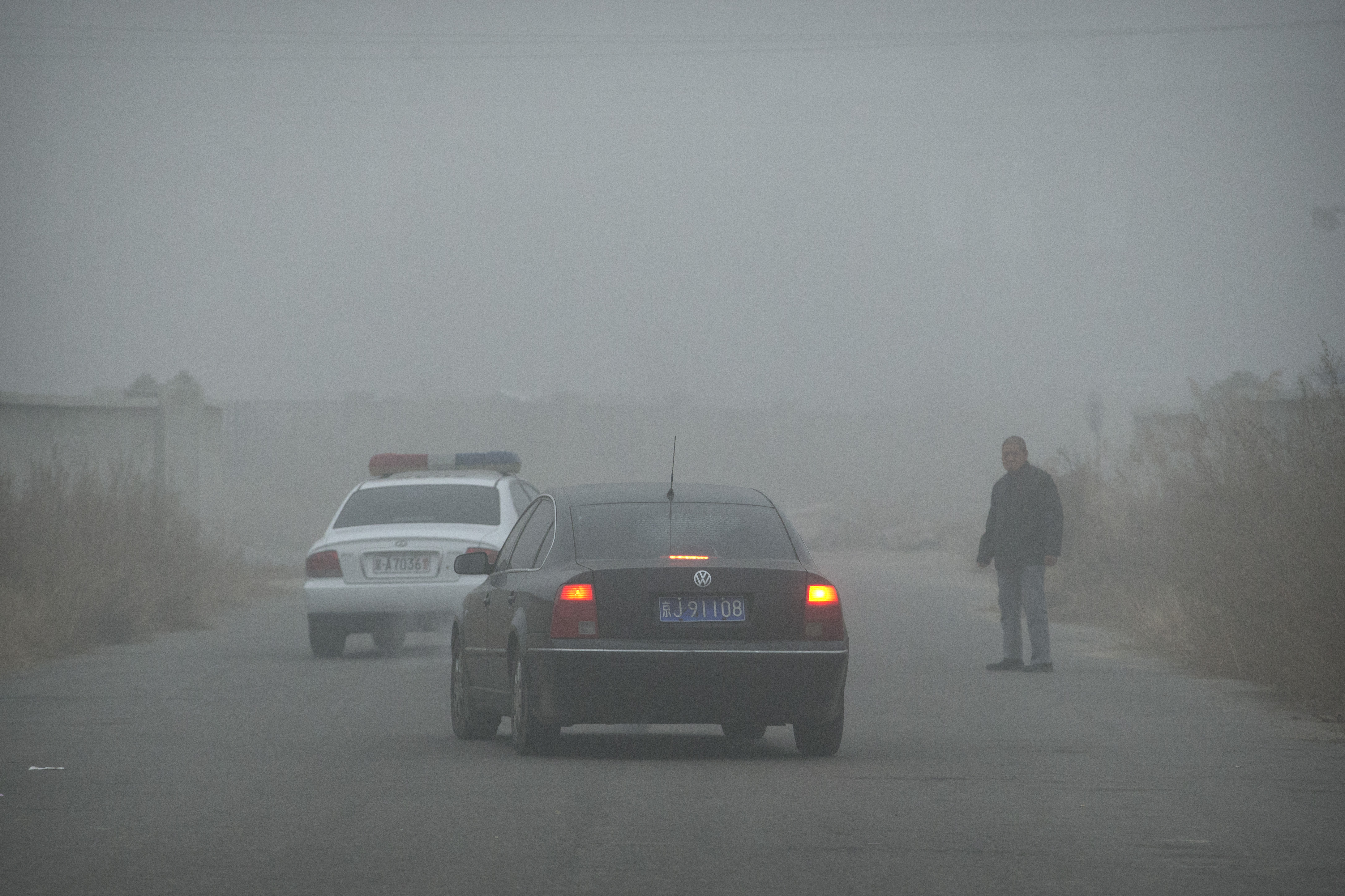 A passerby watches a car as it leaves the Beijing No. 1 Detention Center on the outskirts of Beijing, China, Dec. 22, 2015.