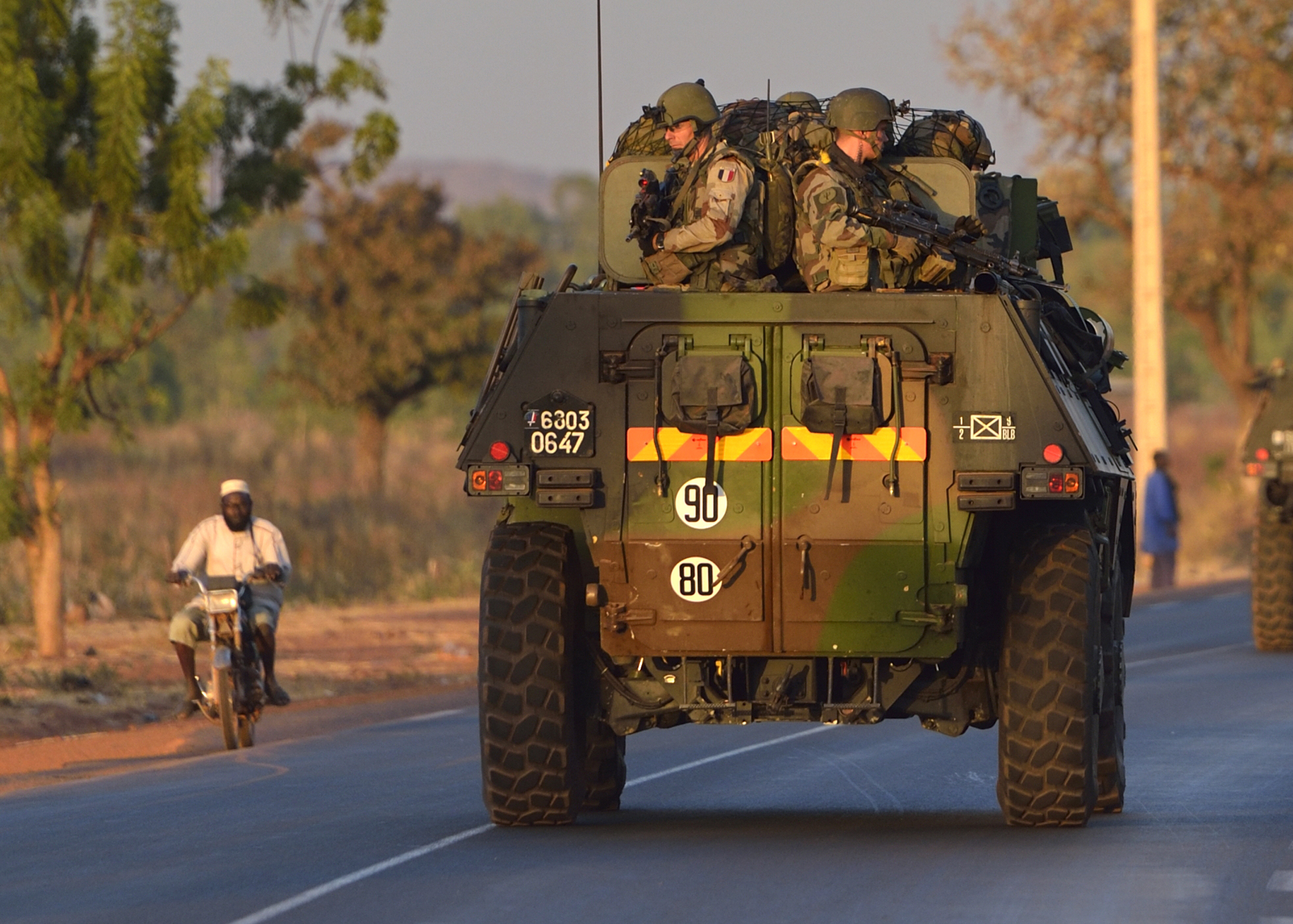"""French army soldiers stand on armored vehicles as they leave Bamako and start their deployment to the north of Mali as part of the """"Serval"""" operations, January 15, 2013."""