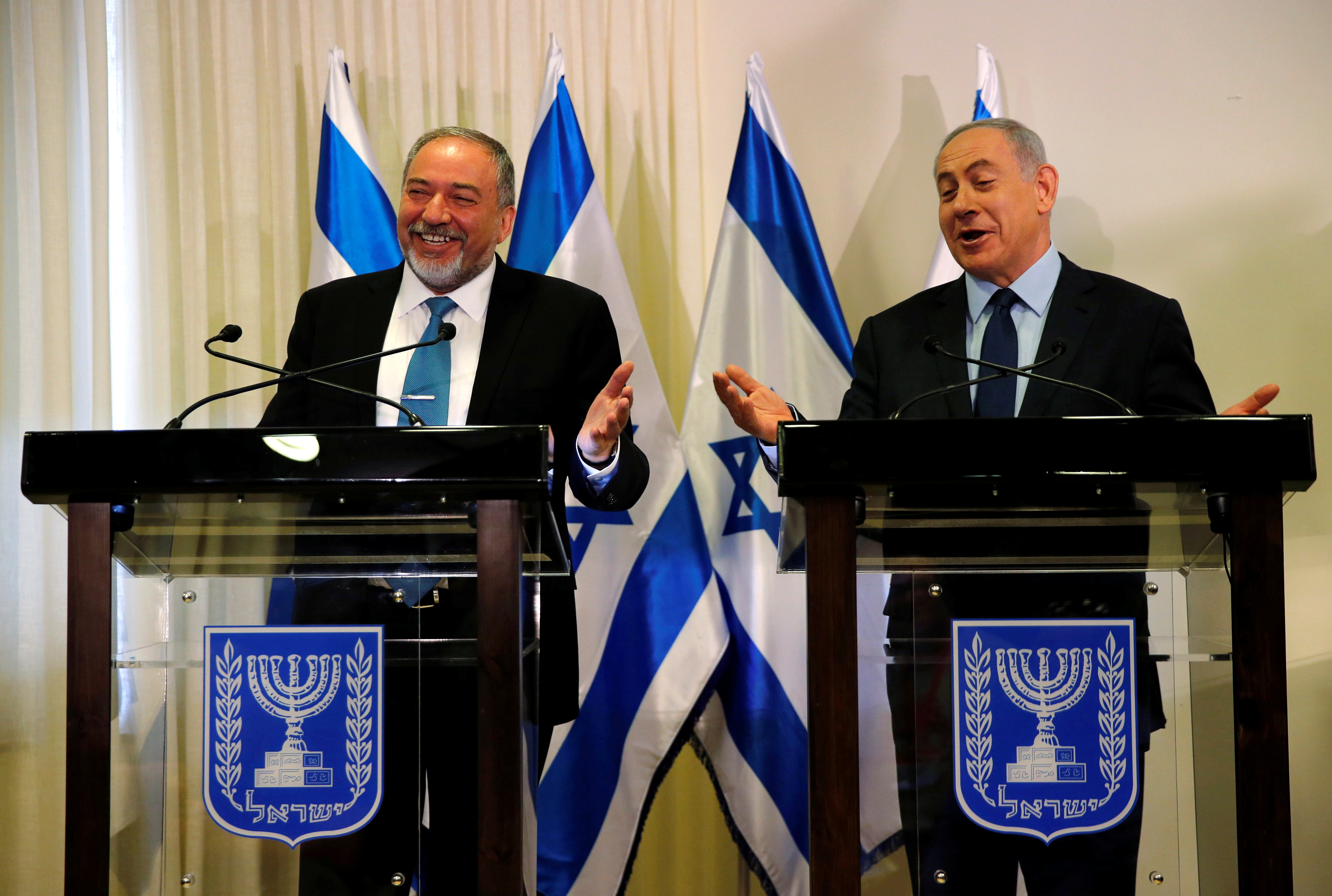 Avigdor Lieberman, head of far-right Yisrael Beitenu party, (L) and Israeli Prime Minister Benjamin Netanyahu deliver statements to the media after signing a coalition deal to broaden the government's parliamentary majority, at the Knesset, the Israe...
