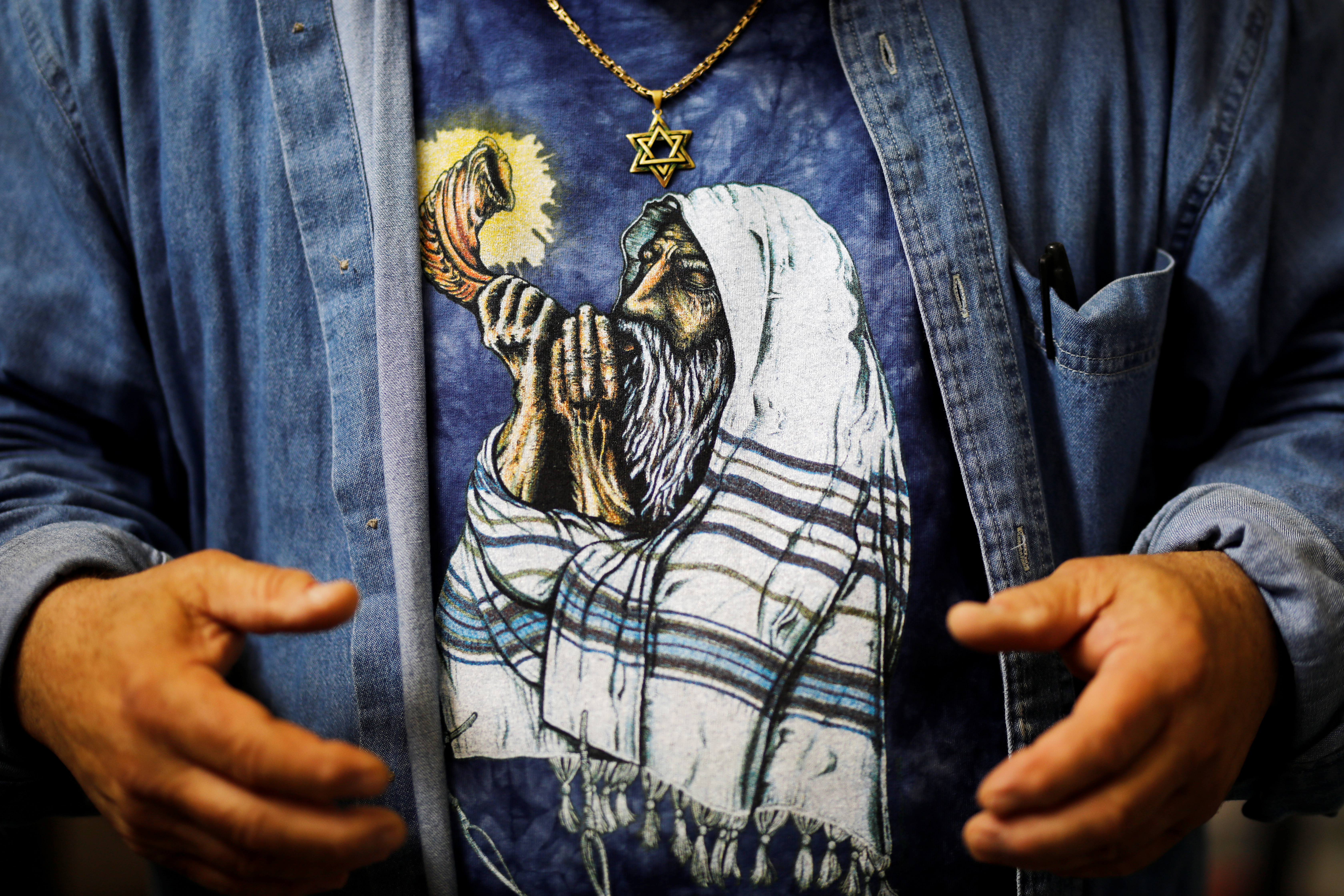 A print of an orthodox Jewish man sounding the Shofar, a ram's horn, is seen on the shirt of Shofar maker Robert Weinger, in his workshop in Rishon Lezion, Israel, Feb. 27, 2018.
