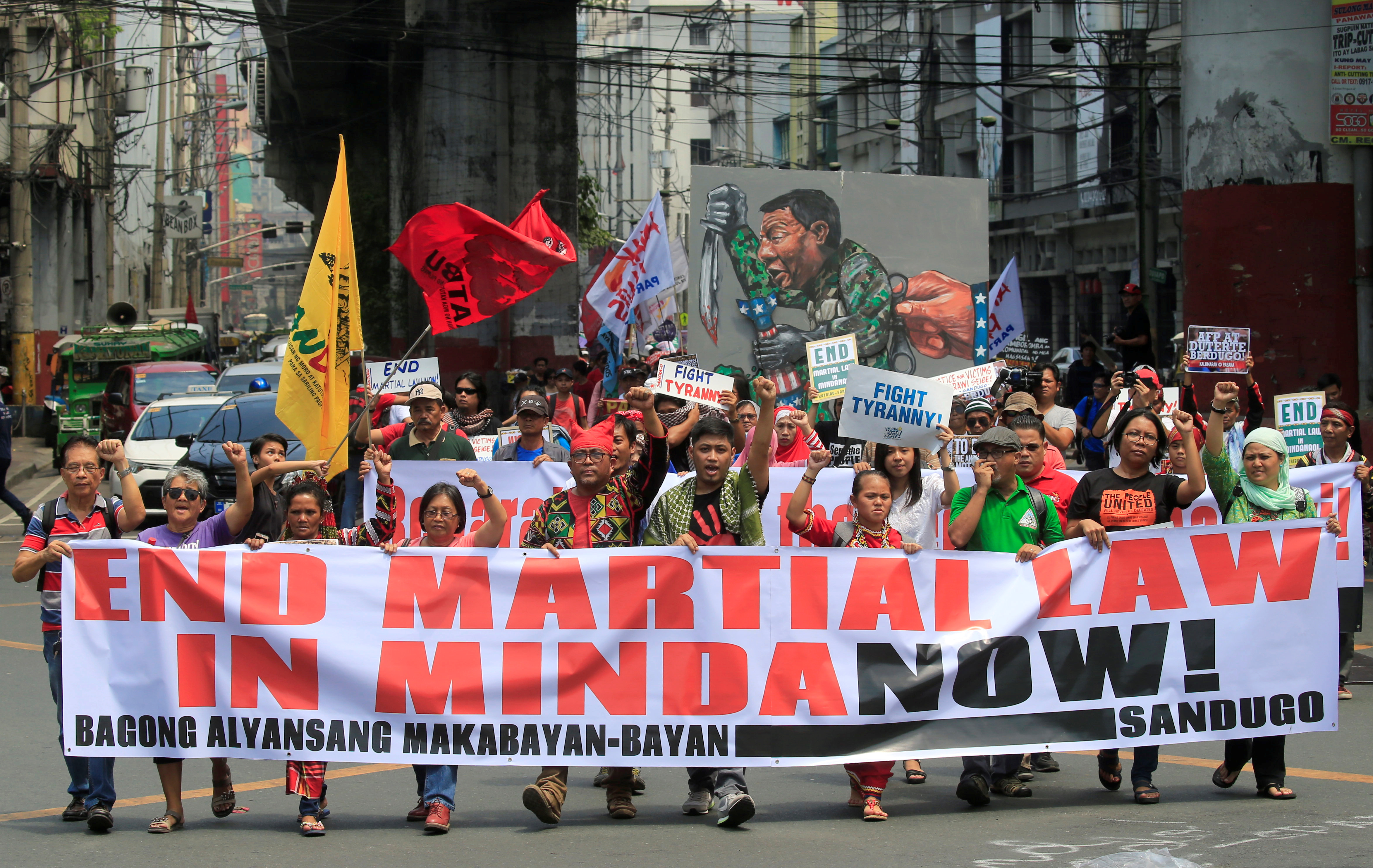 Activists display a banner and a mural of President Rodrigo Duterte to denounced the declaration of martial law in Mindanao island, one year after Islamic militants occupied parts of the southern Philippine city of Marawi during a protest outside the...