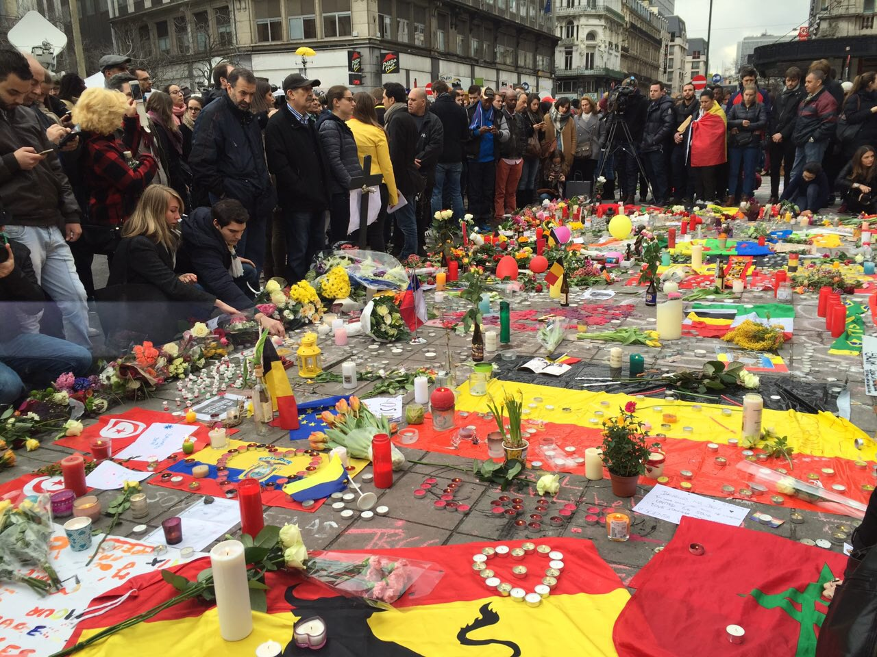 People gather around makeshift memorial in honor of terror attack victims in Brussels, Belgium, March 23, 2016. (N. Pourebrahim/ VOA)
