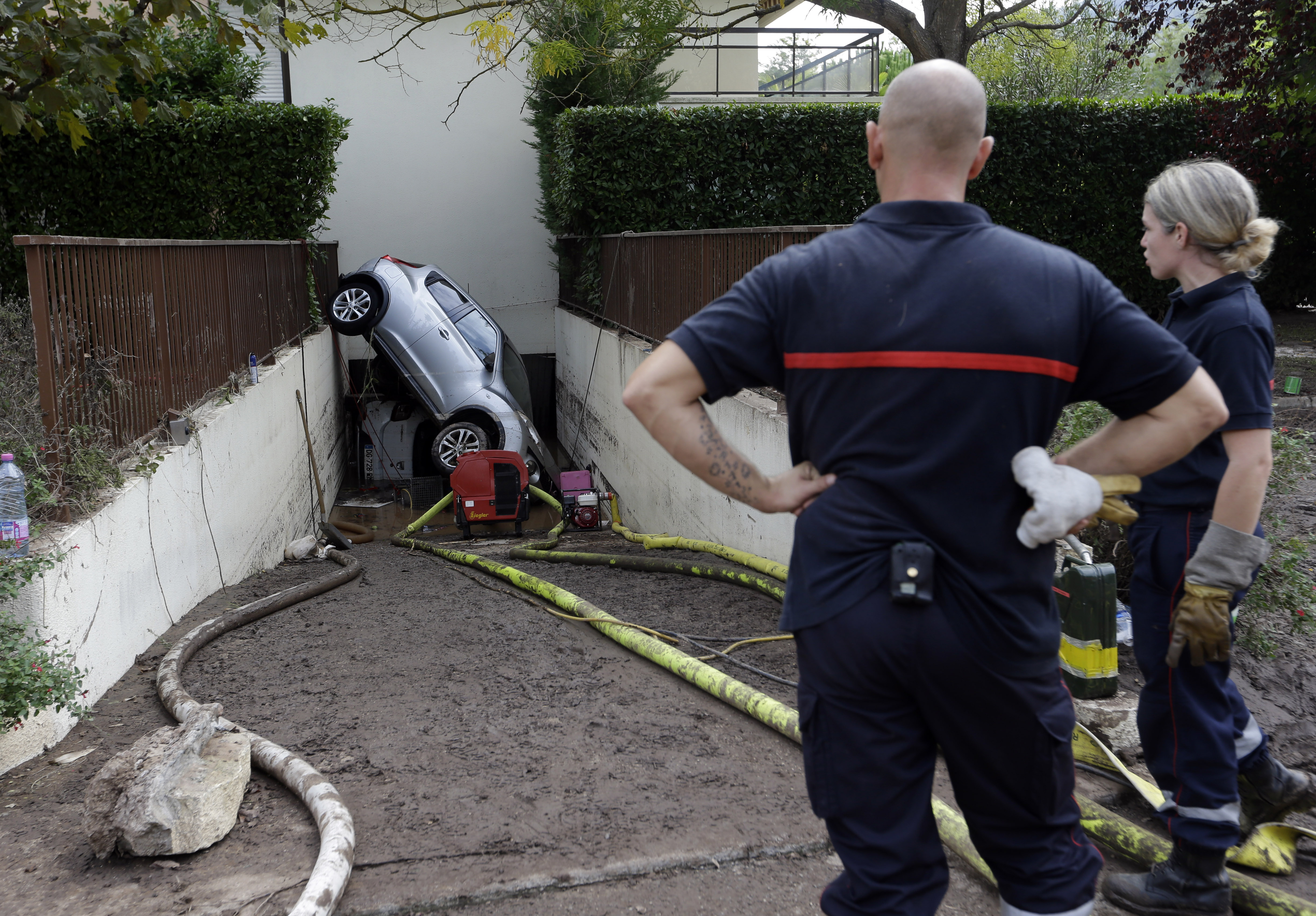 Rescue workers ponder a car stuck in the entrance of an underground garage, in Mandelieu la Napoule, southern France, Oct. 5, 2015.