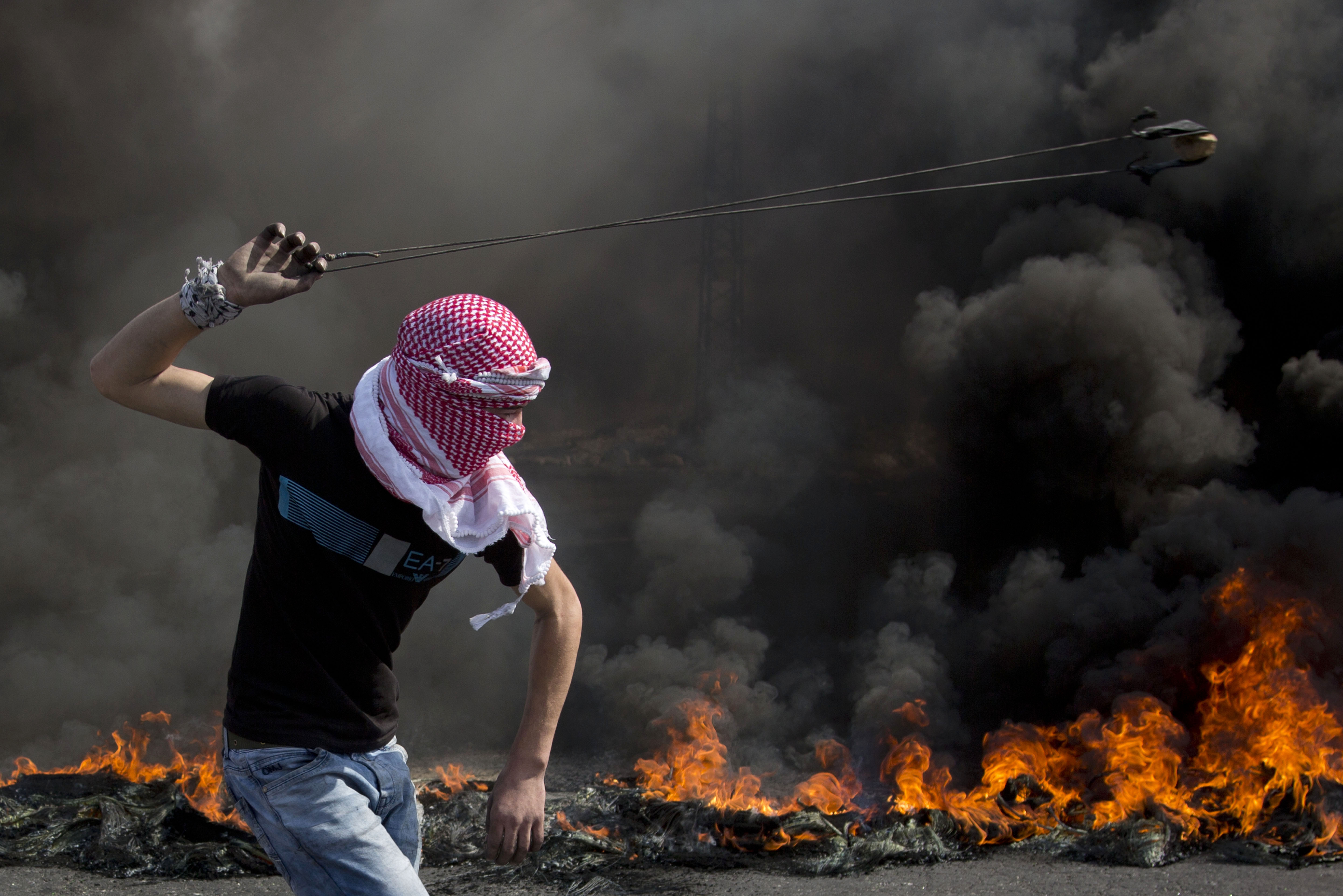 A Palestinian swings a sling during clashes with Israeli troops, near Ramallah, West Bank, Oct. 20, 2015. U.N. Secretary-General Ban Ki-moon called for calm during a surprise visit to Jerusalem on Tuesday.