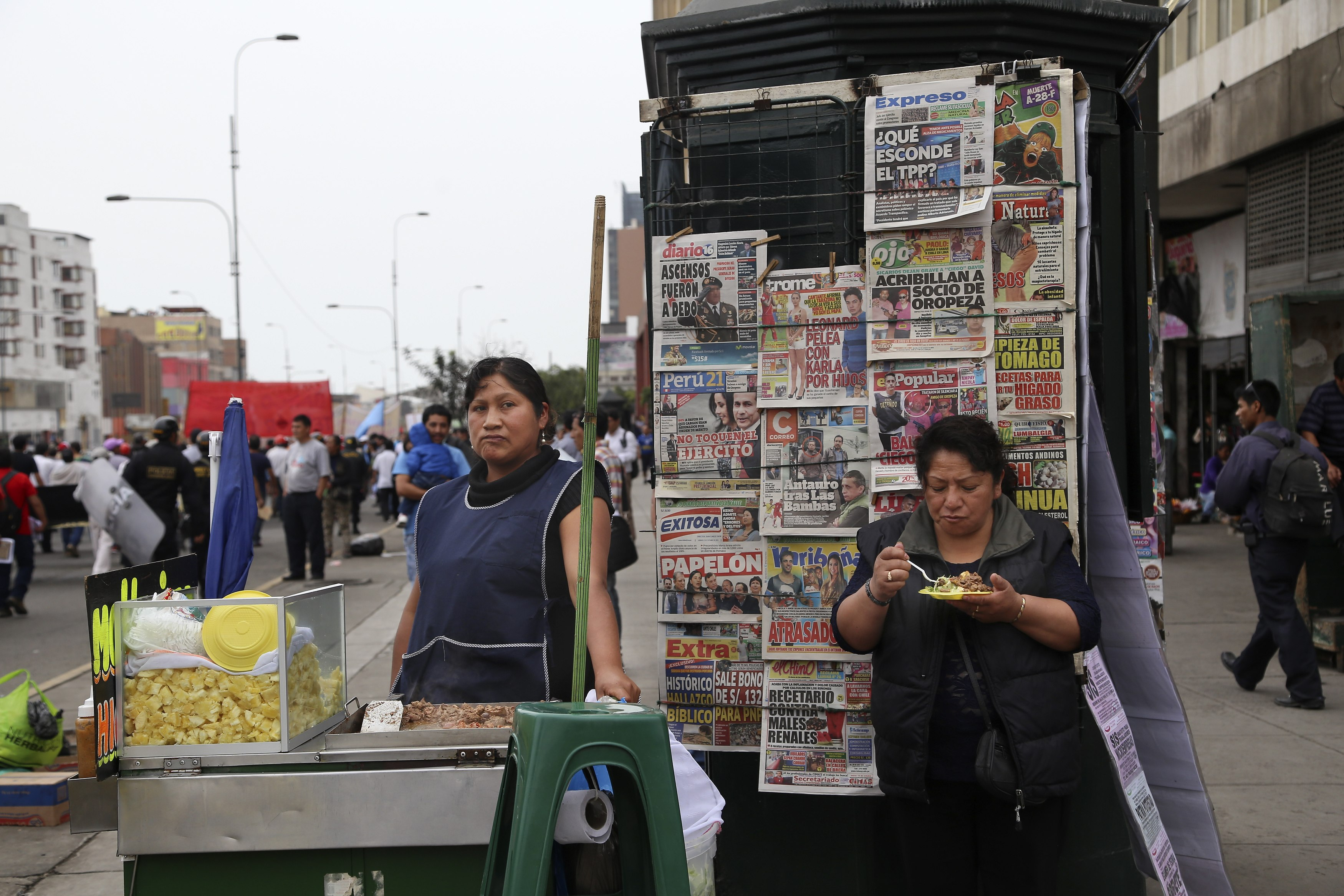 A street vendor waits for clients on the sidelines of a protest against the IMF World Bank, which are holding their annual meetings in Lima, Peru, Oct. 9, 2015.