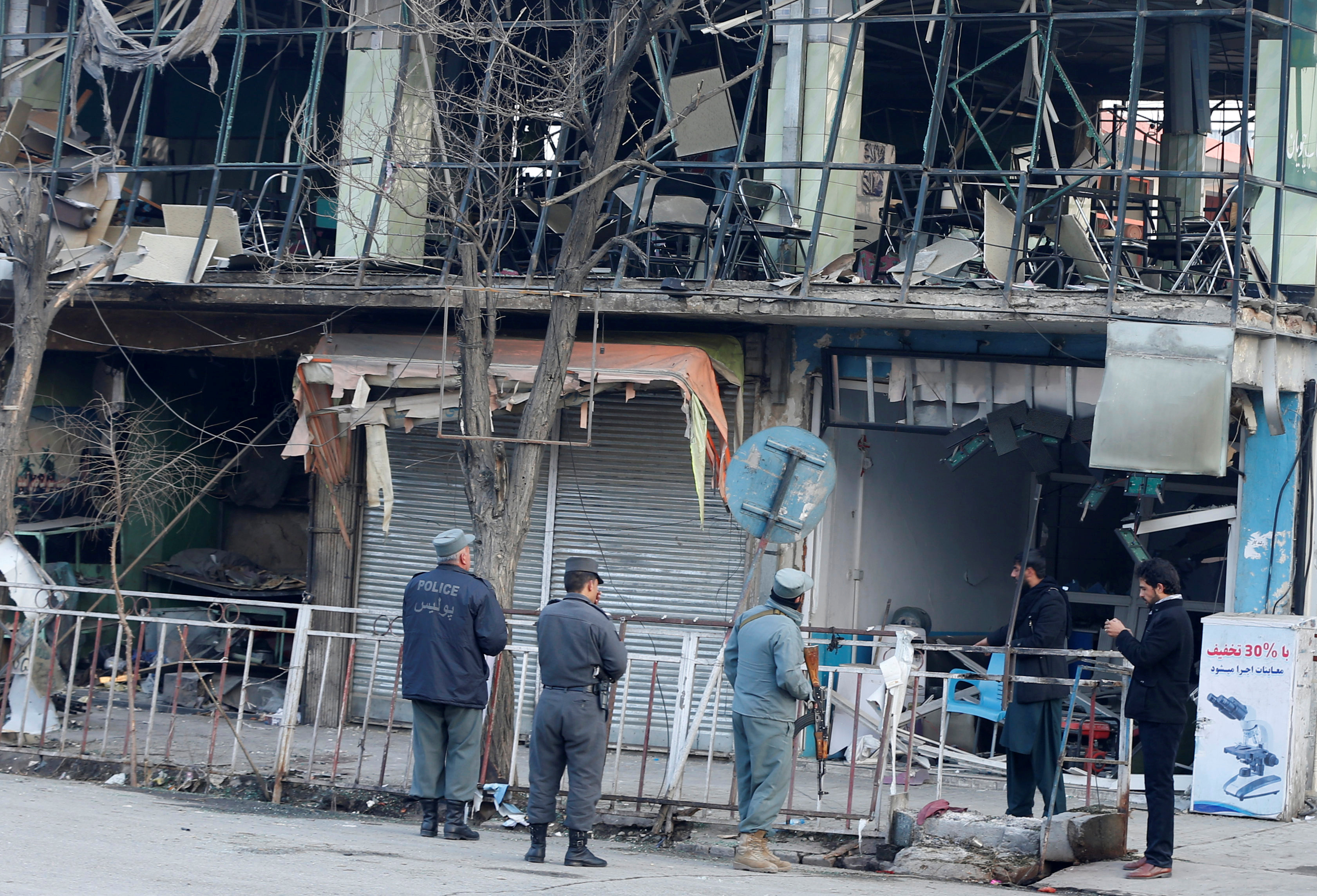 Afghan policemen inspect the site of a bomb attack in Kabul, Afghanistan, Jan.28, 2018. On Saturday, a car bomb ripped through a crowded area outside a government building, killing or wounding hundreds.