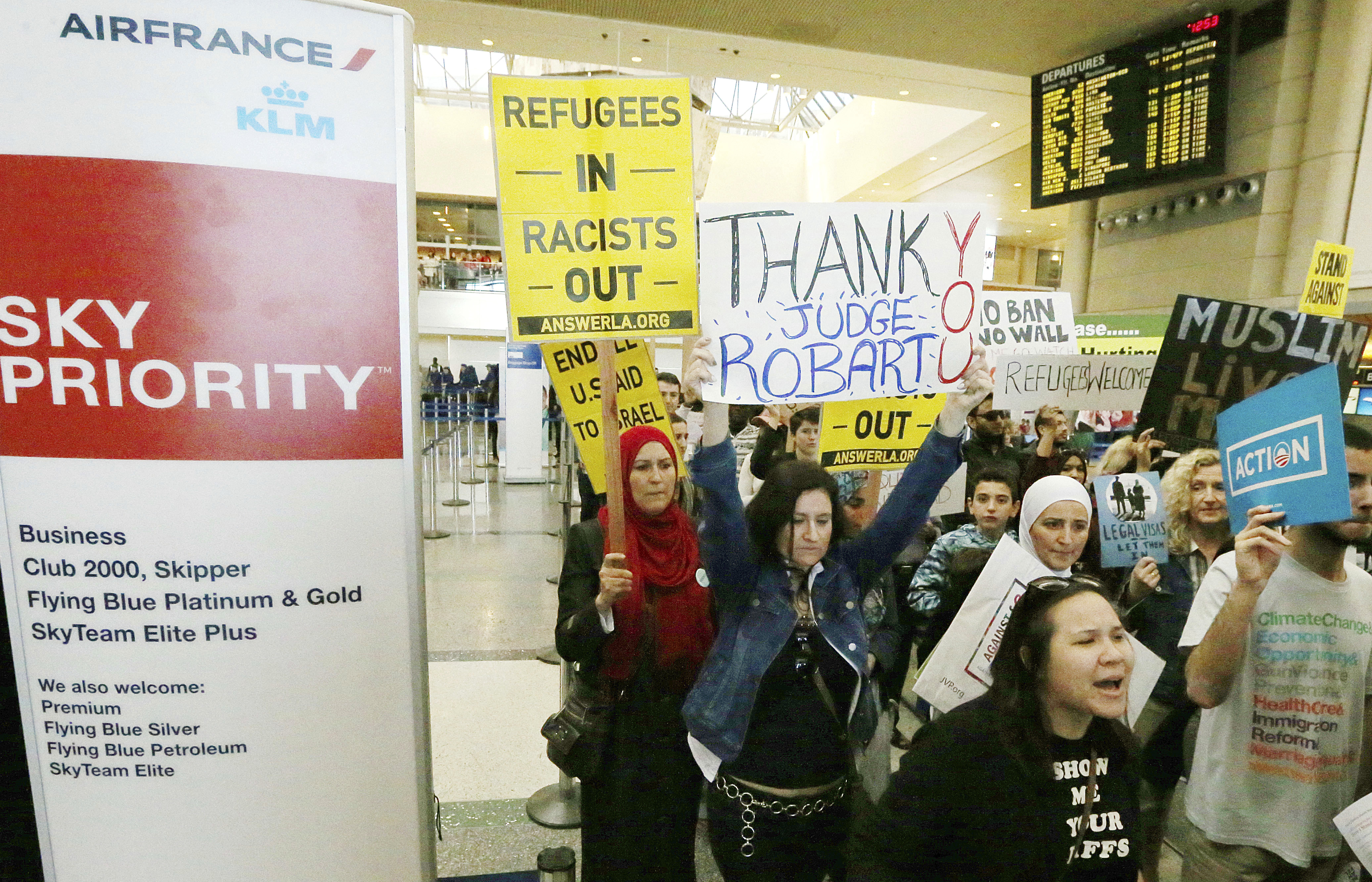 Demonstrators opposed to President Trump's travel ban march through Tom Bradley International Terminal at Los Angeles International Airport, Feb. 4, 2017. One sign thanks federal judge James L. Robart, who issued a stay of the order.
