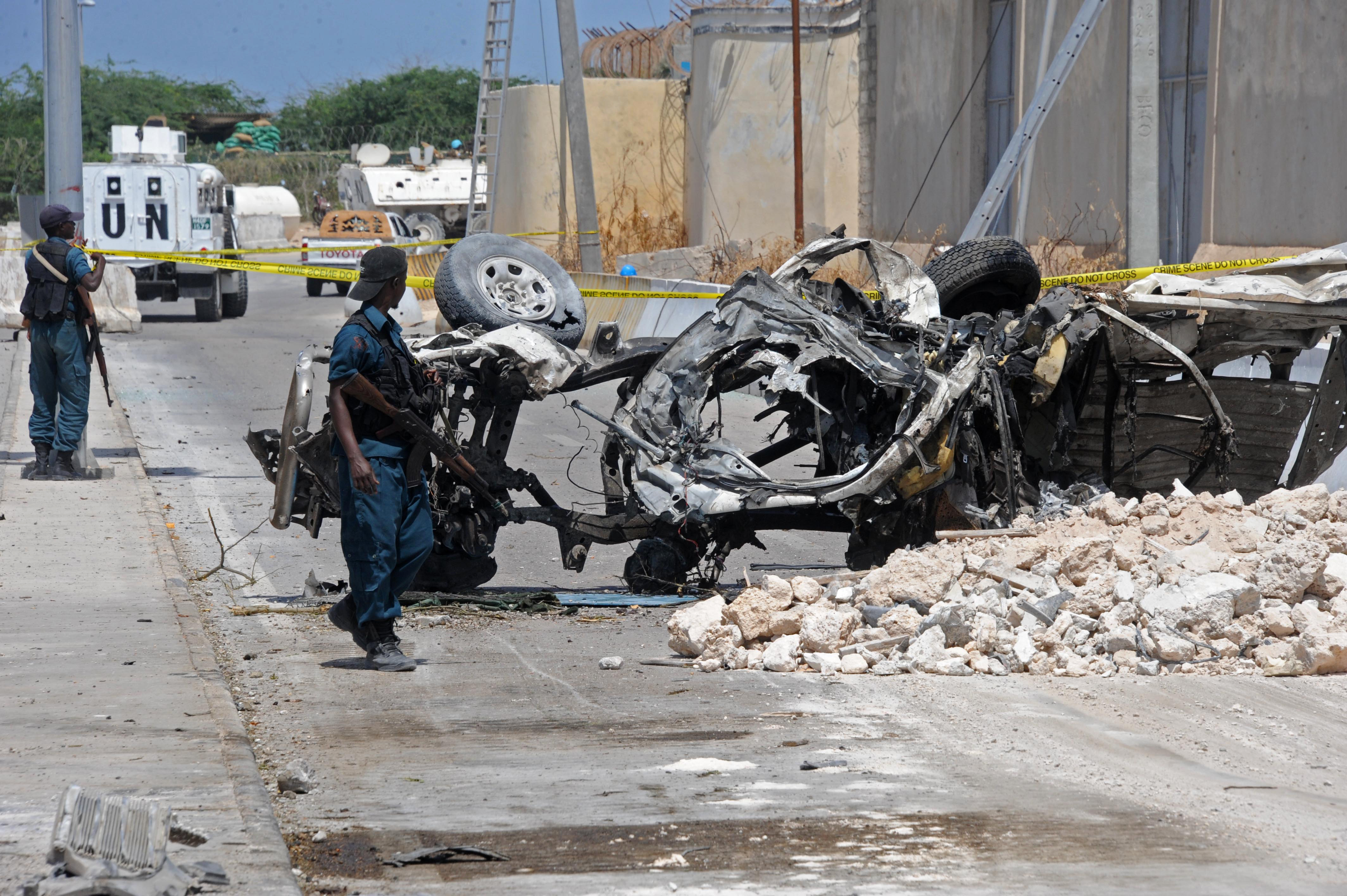 Somali soldiers pass near the wreckage of a car bomb outside the UN's office in Mogadishu on July 26, 2016.