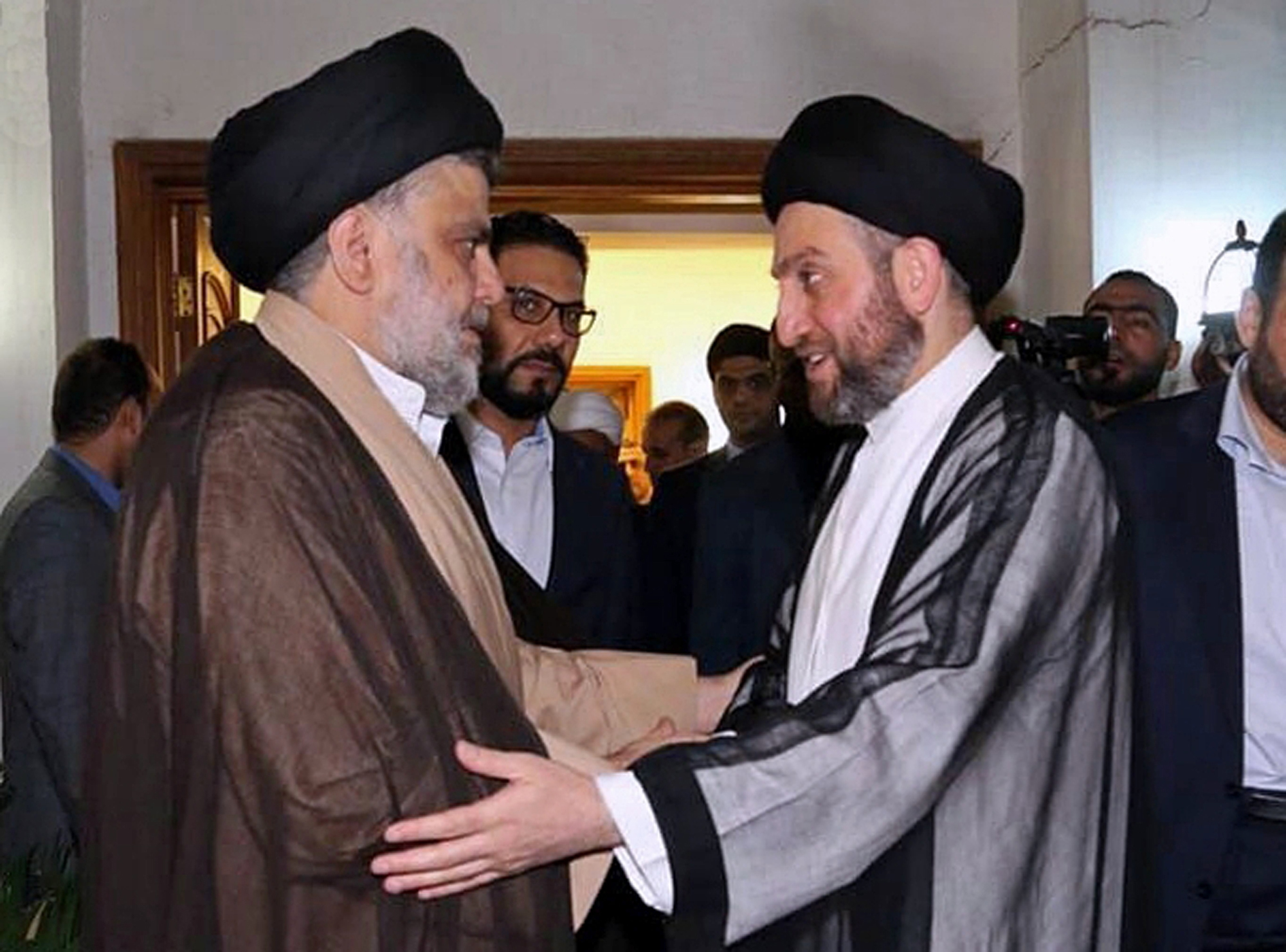 In this photo provided by the Sadr Media Office, Shiite cleric Muqtada al-Sadr, left, greets Shiite leader Ammar al-Hakim on his arrival for their meeting in Baghdad, Iraq, May 22, 2018.