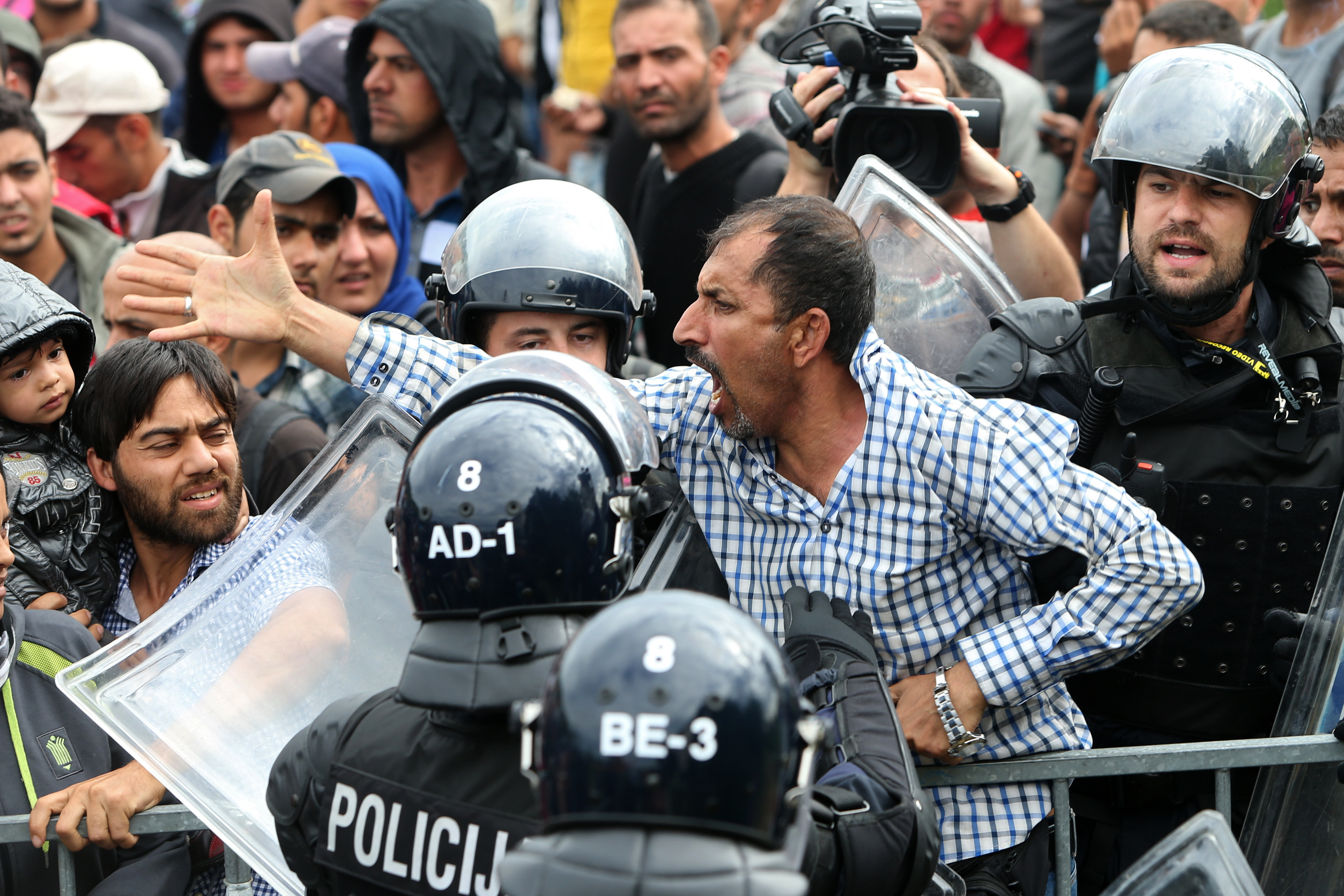 A migrant man reacts as he is surrounded by Slovenian police at the Slovenia-Croatia border crossing in Rigonce, Slovenia, Sept. 19, 2015.