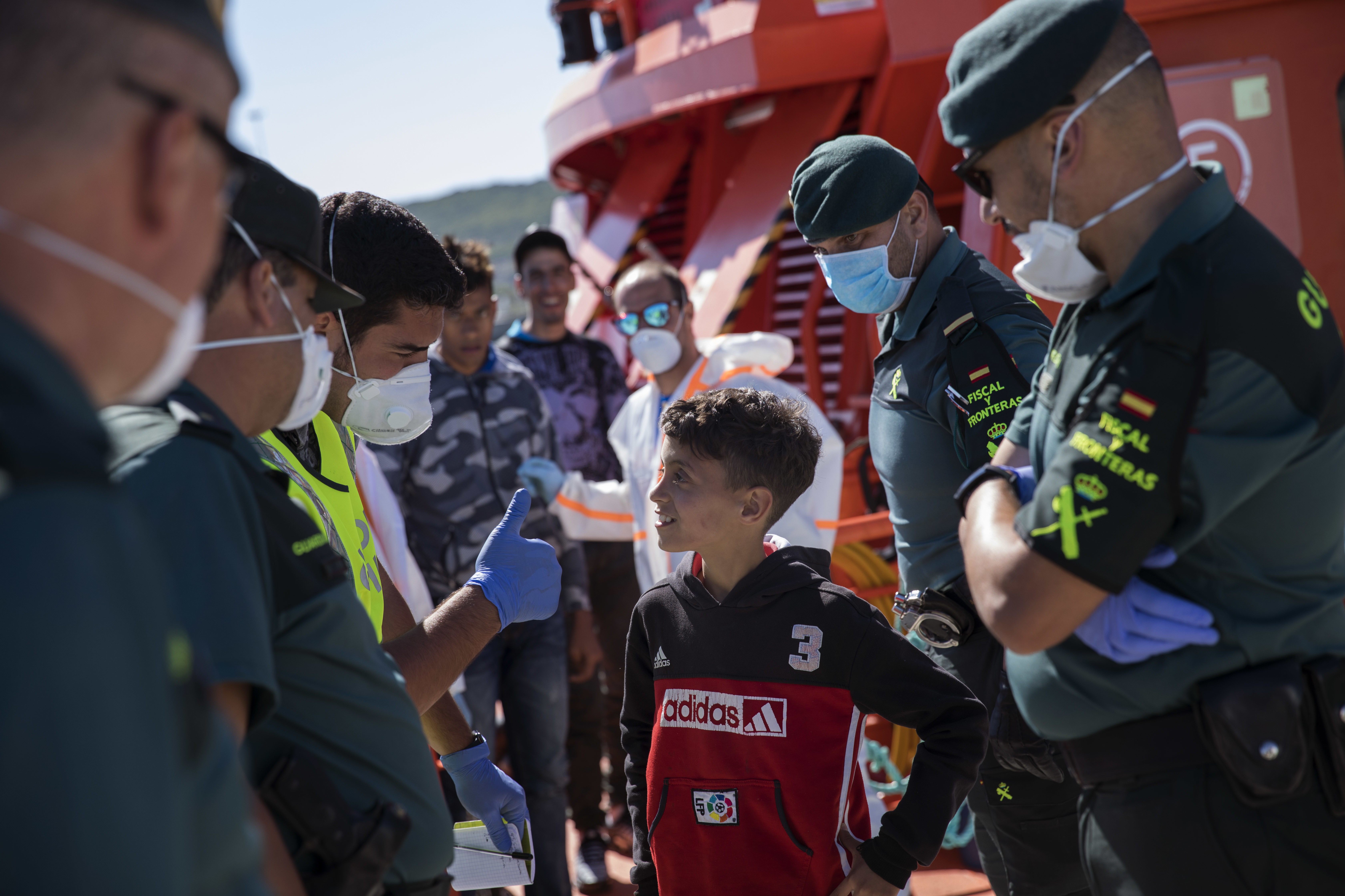 Guardia Civil officers joke with a young migrant disembarking at the port of Barbate, southern Spain, after being rescued by Spain's Maritime Rescue Service in the Strait of Gibraltar, Wednesday, June 27, 2018.